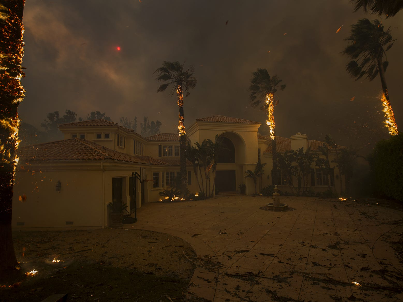 Embers fall from burning palms and the sun is obscured by smoke as flames close in on a house at the Woolsey Fire, Friday.