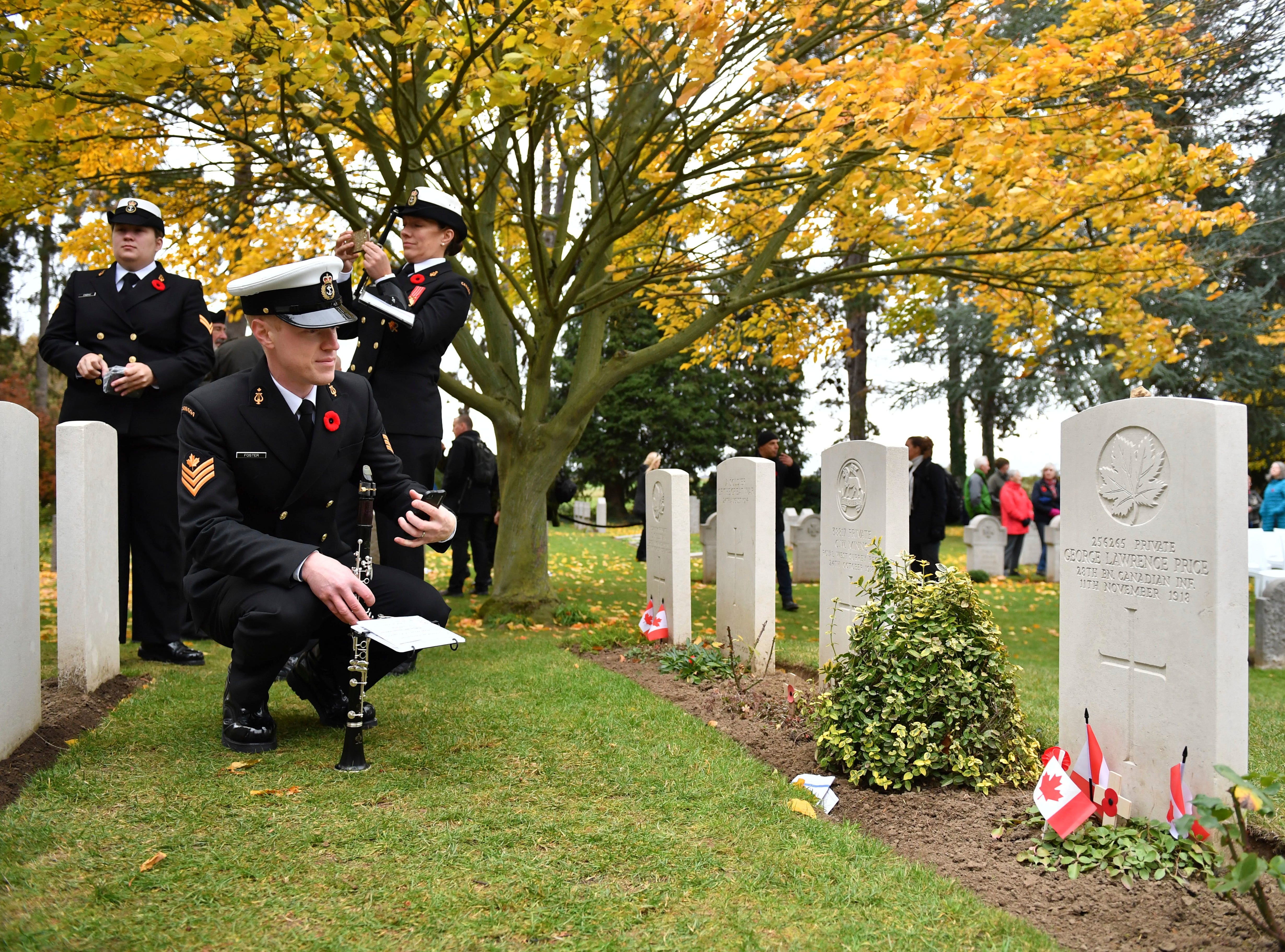 A Canadian soldier looks at the grave of Canadian World War I soldier George Lawrence Price at the St. Symphorien cemetery in Mons, Belgium, Saturday, Nov. 10, 2018. George Price was the last Canadian soldier to die in World War I.