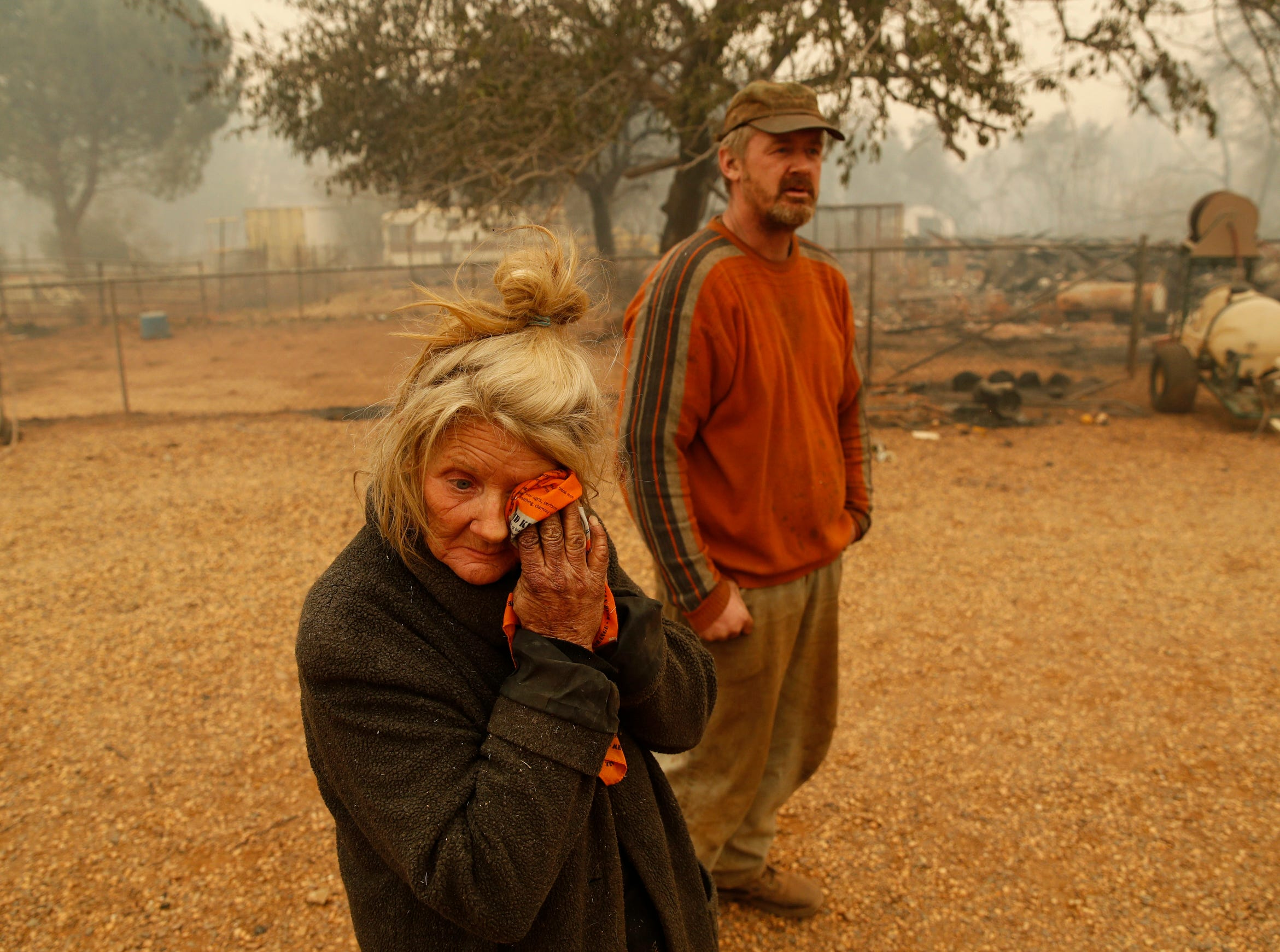"Cathy Fallon wipes her face beside her son Gabriel Fallon as she stands near the charred remains of her home Friday, in Paradise, Calif. ""I'll be darned if I'm gonna let those horses burn in the fire"" said Fallon, who stayed on her property to protect her 14 horses, ""It has to be true love."" All of the horses survived."