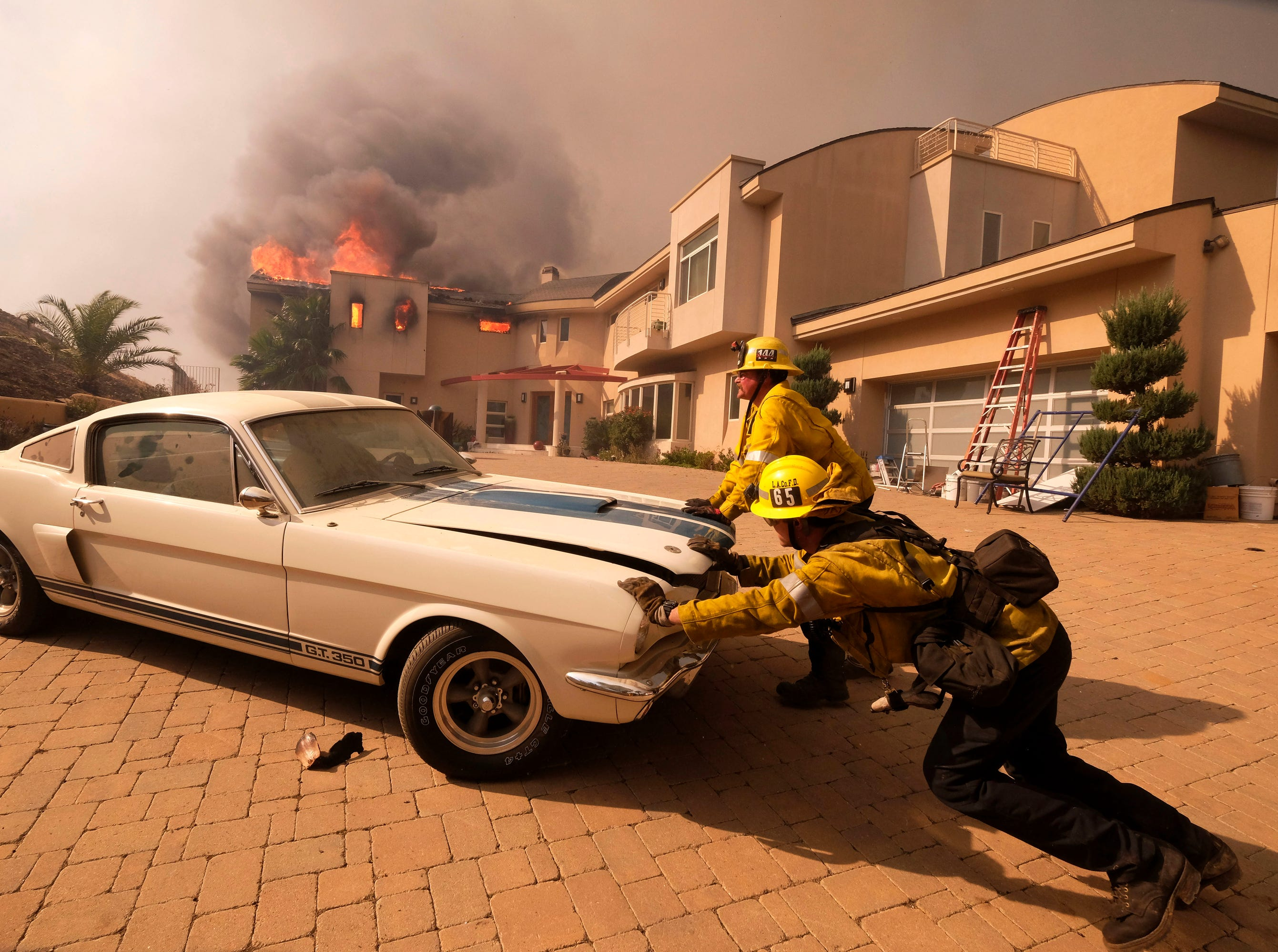 Firefighters push a vehicle from a garage as a wildfire fire burns a home near Malibu Lake in Malibu, Calif.