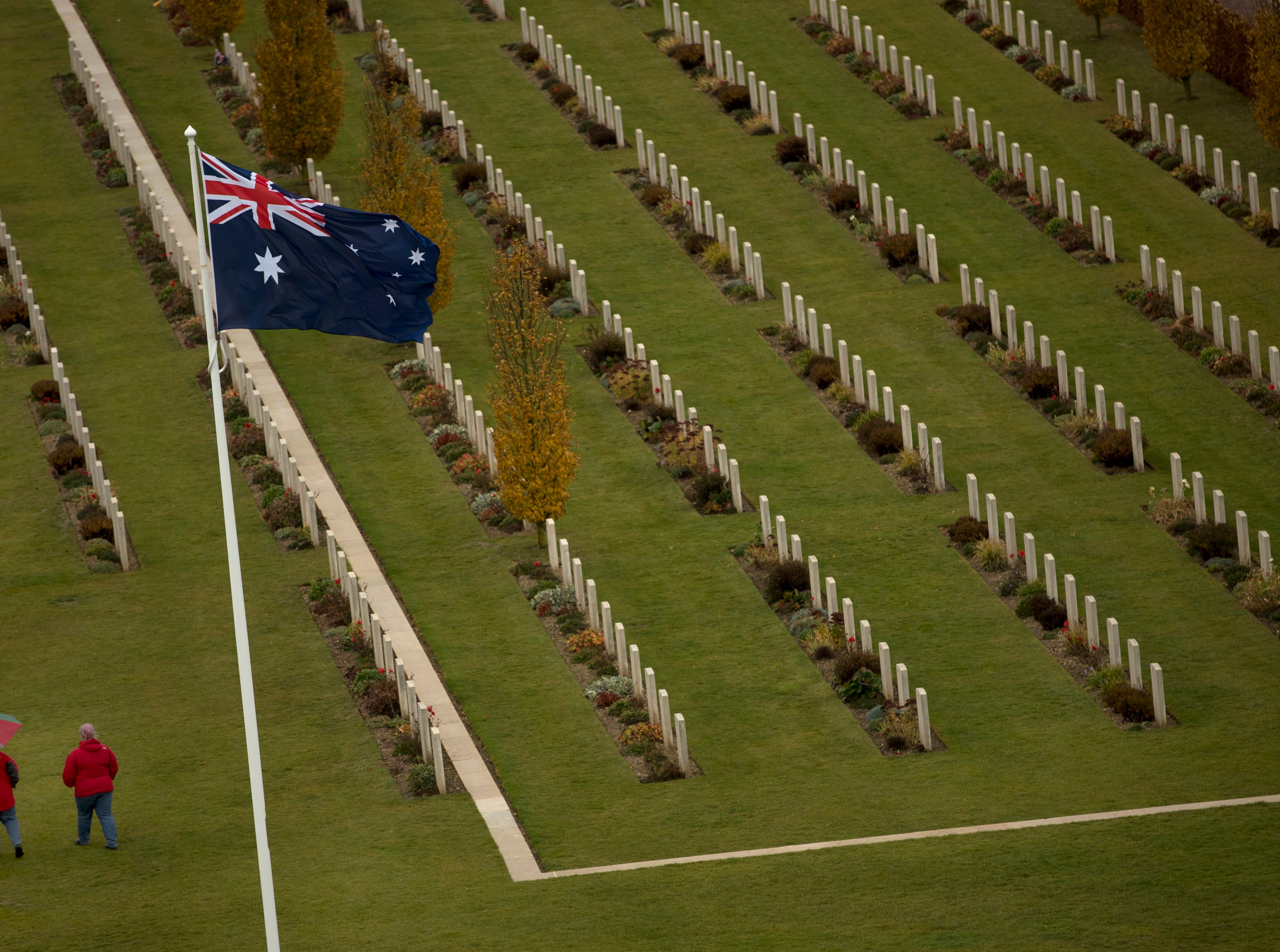 Two visitors walk among the headstones at the World War I Australian National Memorial in Villers-Bretonneux, France, Saturday, Nov. 10, 2018. The memorial walls at the site bear the names of 11,000 missing Australian soldiers who died in France during World War I.