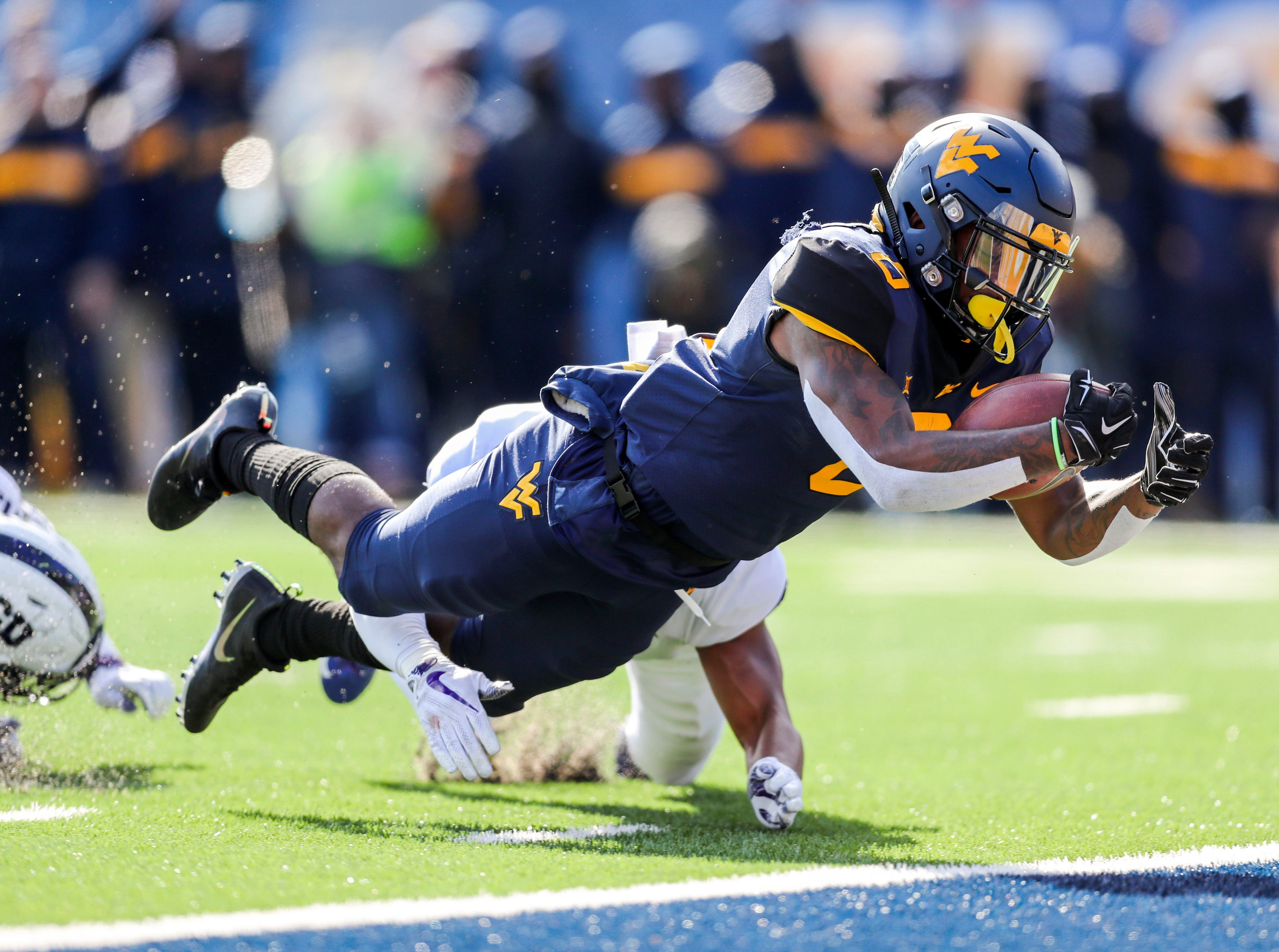 West Virginia Mountaineers running back Kennedy McKoy (6) runs for a touchdown during the second quarter against the TCU Horned Frogs at Mountaineer Field at Milan Puskar Stadium.