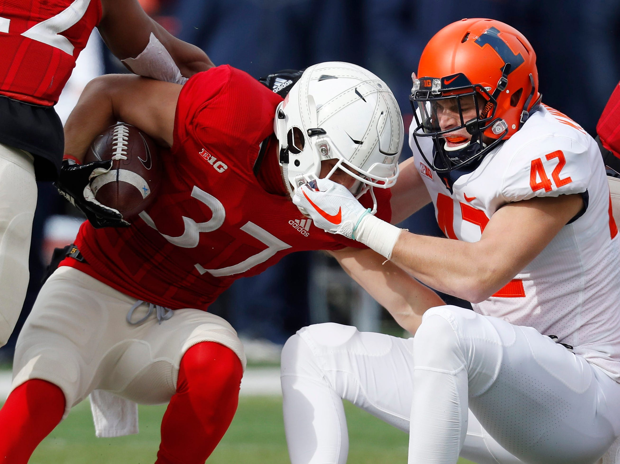 Illinois Fighting Illini defensive back Michael Marchese (42) grabs the facemask of Nebraska Cornhuskers running back Wyatt Mazour (37) in the first half at Memorial Stadium.
