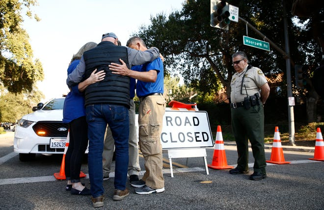 Chaplain Manuel Castro, right, prays with activists Sandy and Lonnie Phillips at a police barricade near the mass shooting site at the Borderline Bar and Grill on Friday, Nov. 9, 2018, in Thousand Oaks, Calif. The Phillips lost their daughter, Jessica Ghawi, when she was murdered in a movie theater shooting in Aurora, CO.