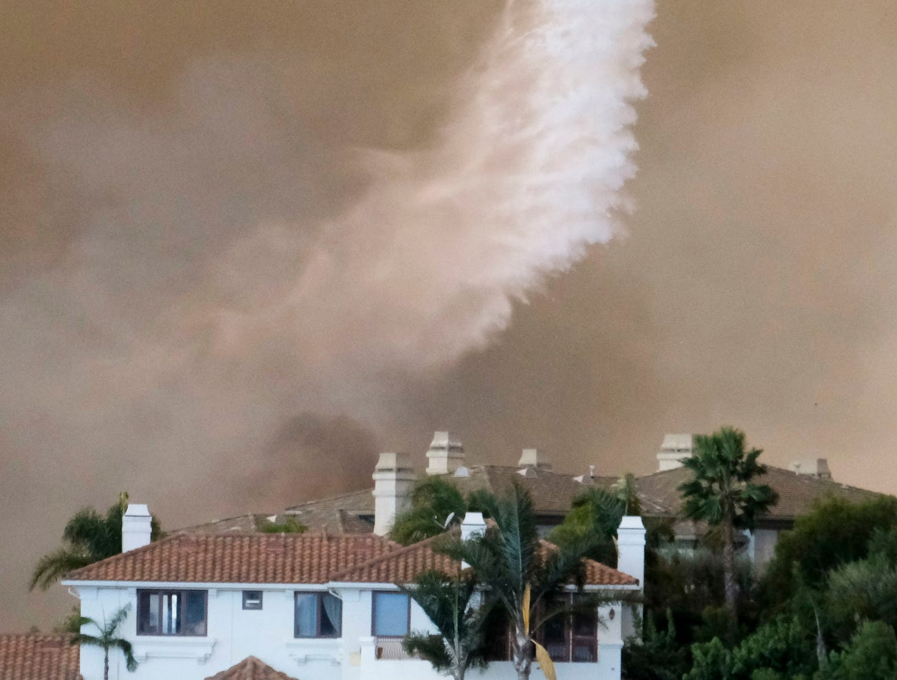 A helicopter drops water on a brush fire behind a home during the Woolsey Fire in Malibu, Calif., Friday.
