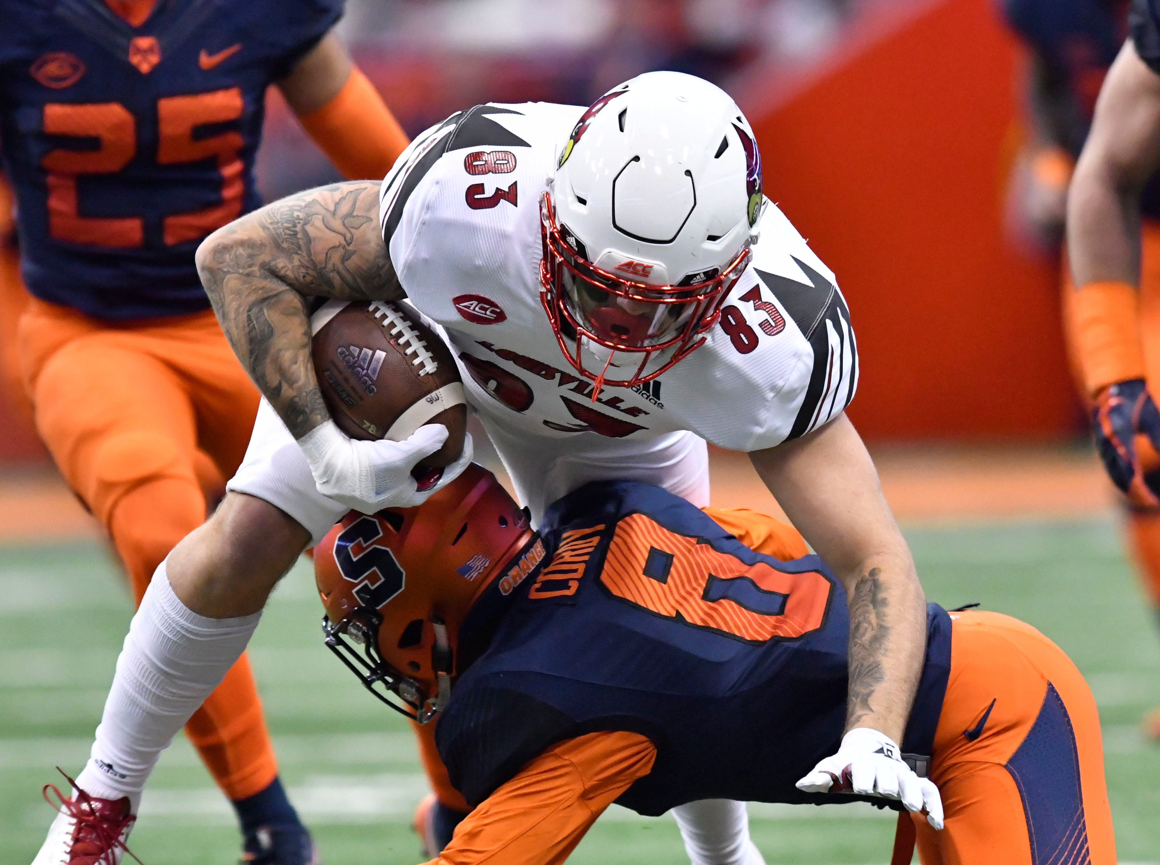 Louisville Cardinals tight end Micky Crum (83) is tackled by Syracuse Orange defensive back Antwan Cordy (8) after making a catch during the first quarter at the Carrier Dome.