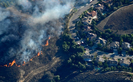 Fires burn toward homes on, Nov. 9, 2018, as seen from a helicopter over the Calabasas section of Los Angeles. Flames driven by powerful winds torched dozens of hillside homes in Southern California, burning parts of tony Calabasas and mansions in Malibu and forcing tens of thousands of people — including some celebrities — to flee as the fire marched across the Santa Monica Mountains toward the sea.