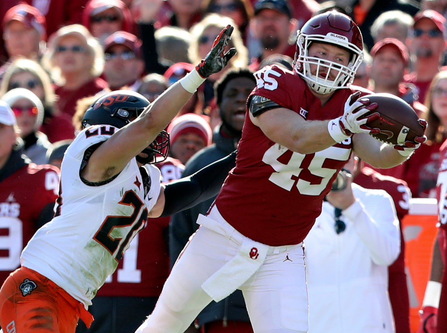 Oklahoma Sooners fullback Carson Meier (45) makes a catch past Oklahoma State Cowboys safety Malcolm Rodriguez (20) during the first quarter at Gaylord Family-Oklahoma Memorial Stadium.
