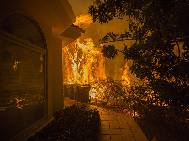 Flames approach a house, Friday with a loud roaring sound, during the Woolsey Fire on in Malibu, Calif.
