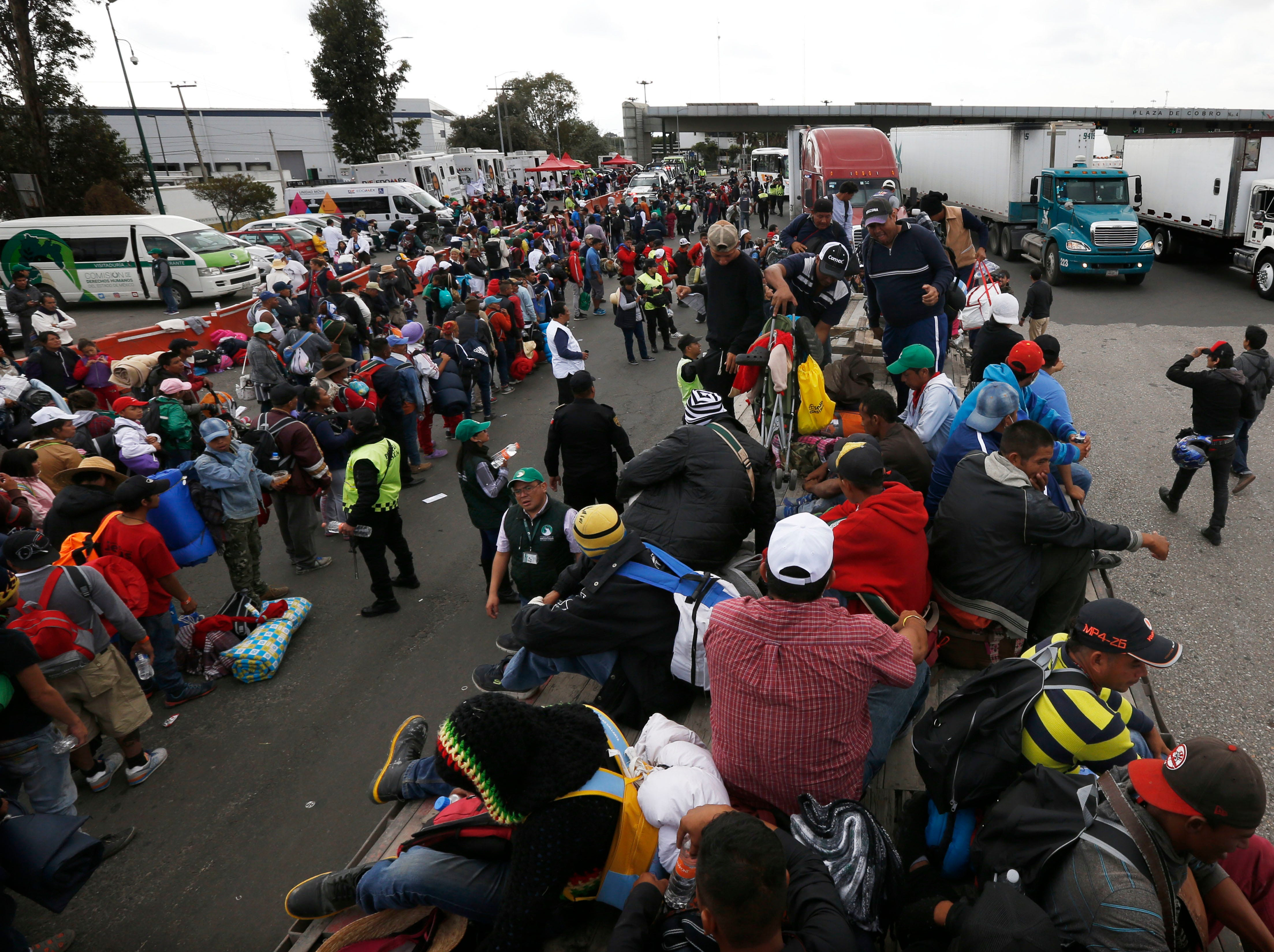 Central American migrants stand in line hoping to hitch a ride in Tepotzotlan, Mexico, as they resume their journey north after leaving the temporary shelter at the Jesus Martinez stadium, Saturday, Nov. 10, 2018. Thousands of Central American migrants were back on the move toward the U.S. border Saturday, after dedicated Mexico City metro trains whisked them to the outskirts of the capital and drivers began offering rides north.
