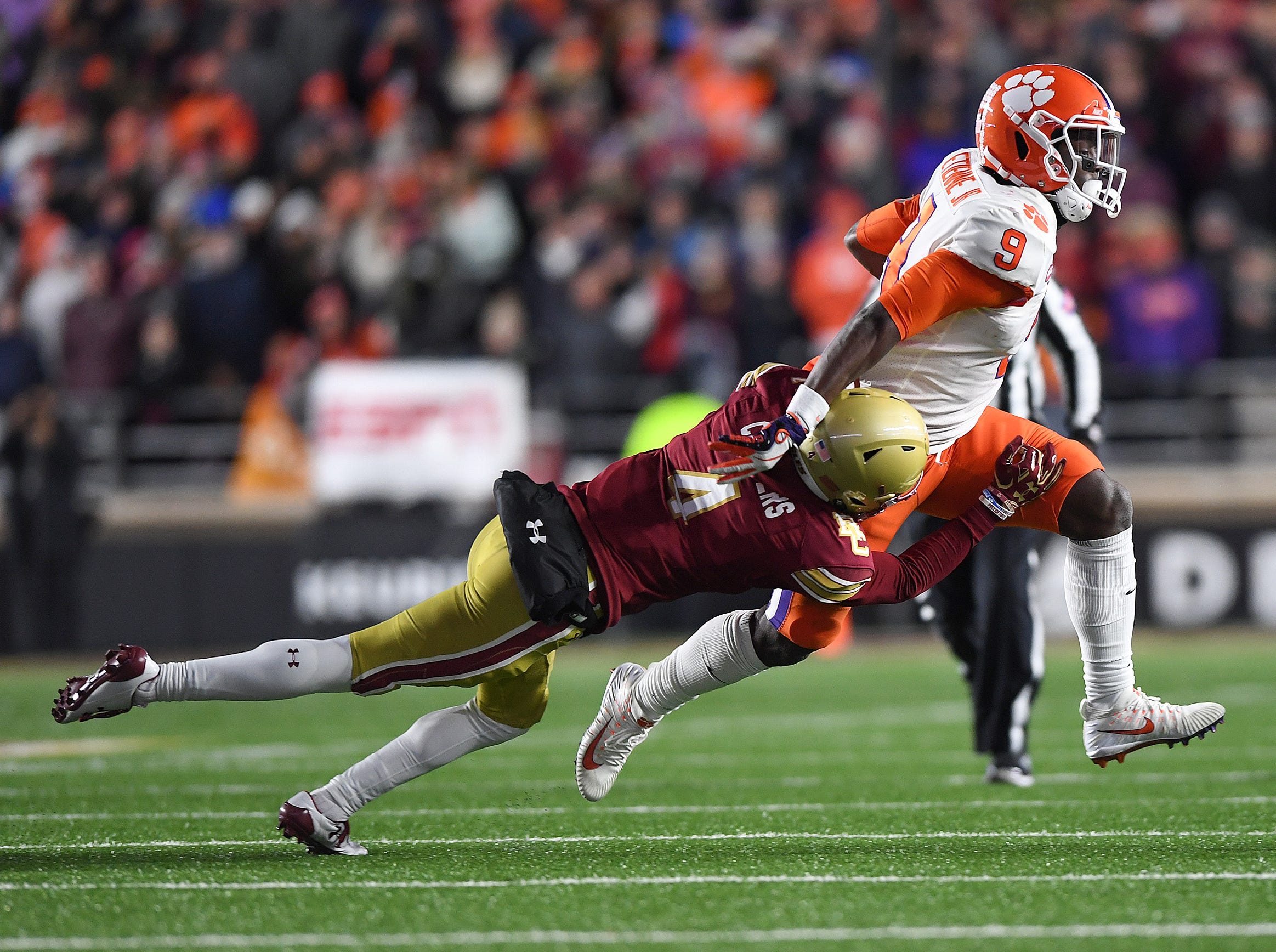 Boston College defender Hamp Cheevers (4) tries to bring down Clemson running back Travis Etienne (9) during the 2nd quarter at Boston College's Alumni Stadium in Chestnut Hill, MA. Saturday, November 10, 2018.