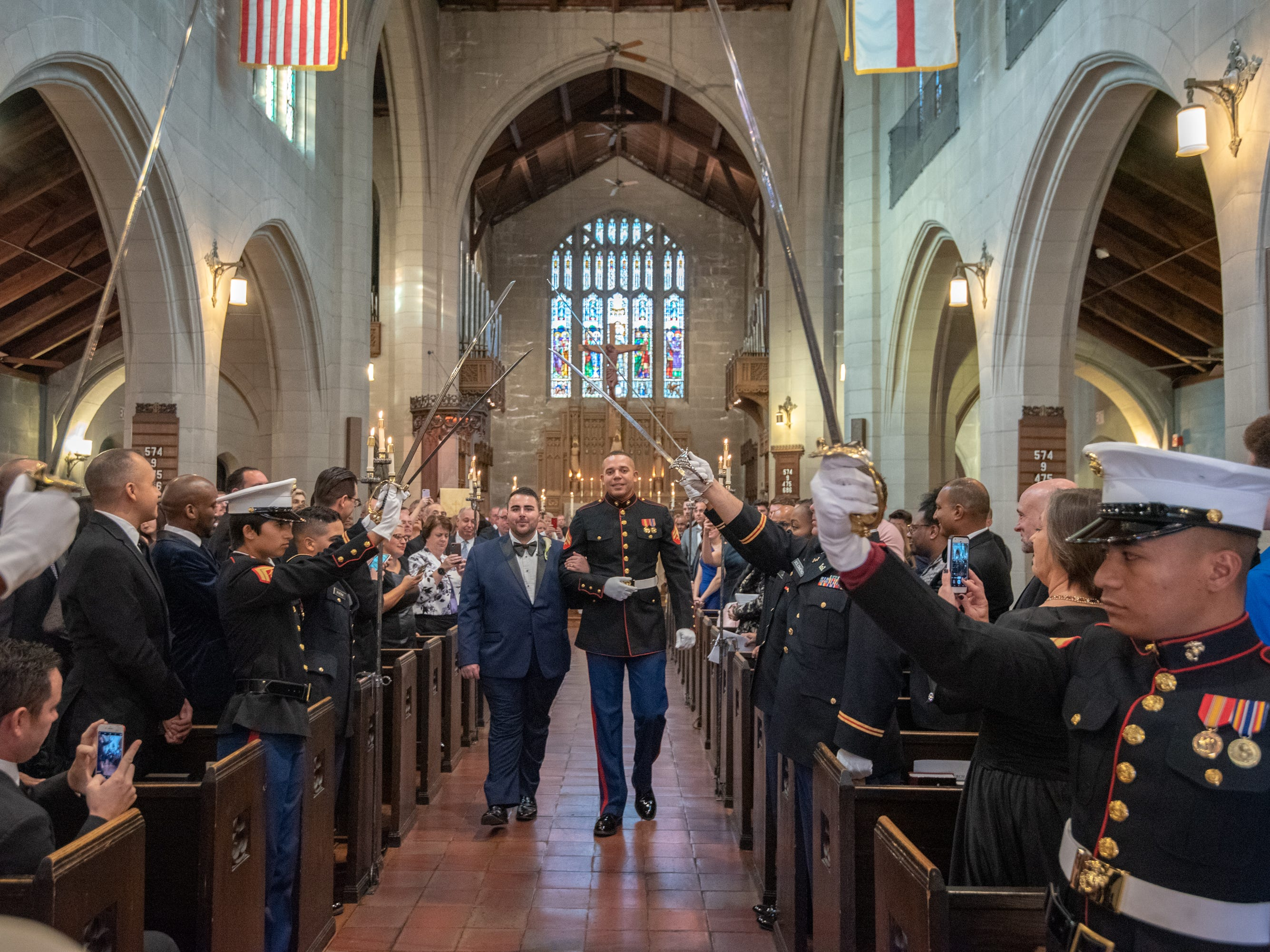 Christian Fuscarino, (left) Executive Director of Garden State Equality, and U.S. Marine Corporal Aaron Williams (in uniform) were married at Trinity Church in Asbury Park on Sunday, November 11, 2018. Here, they pass under the raised swords at the end of the ceremony.