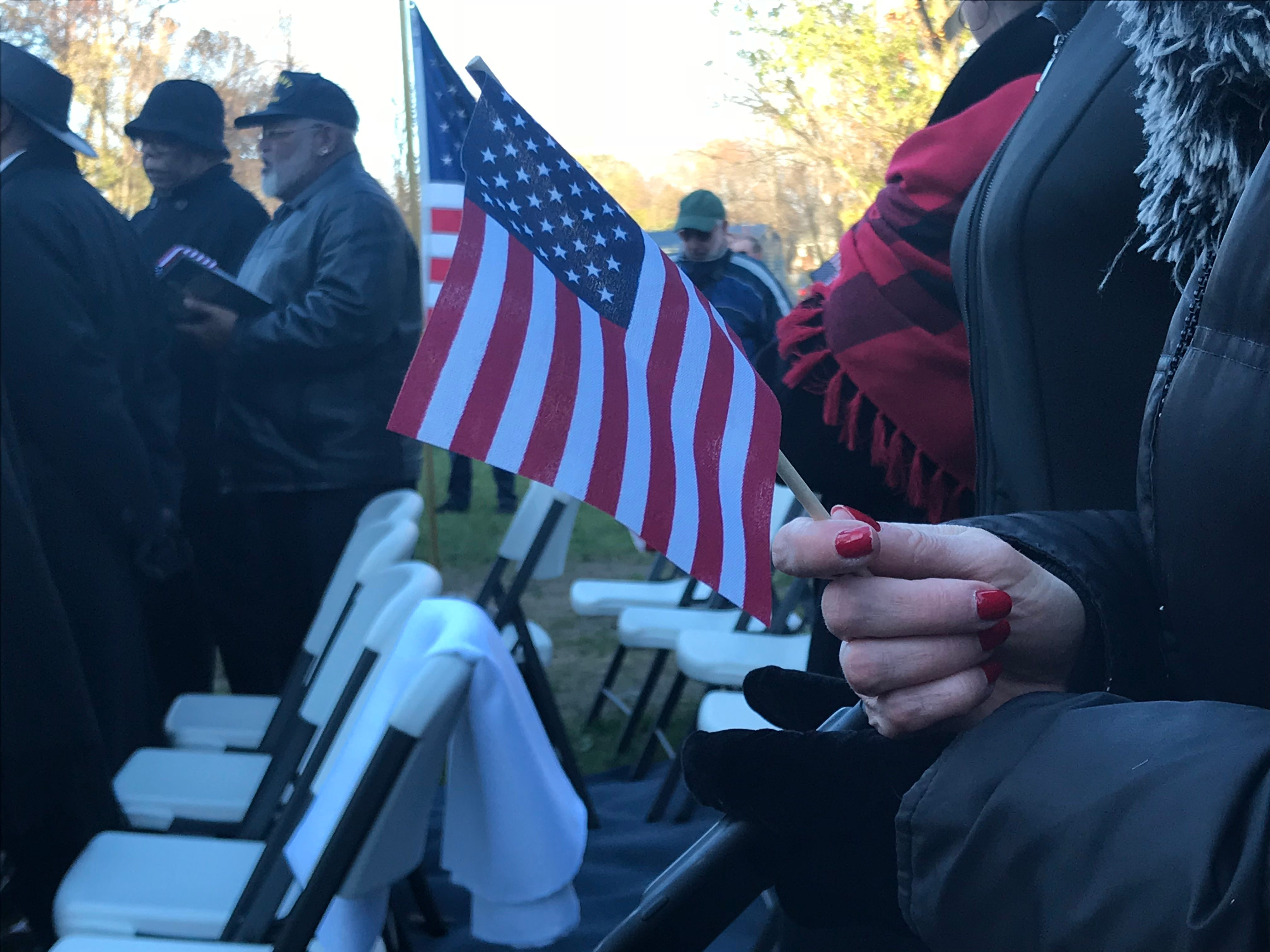 """Assemblywoman Joann Downey holds up an American flag as the Bethel AME Church choir sings Nov. 11, 2018, at Veterans Park in Freehold Borough. More than 100 people attended the ceremony, which commemorated Bigerton """"Buddy"""" Lewis Jr. and his five brothers, who all served in World War II."""
