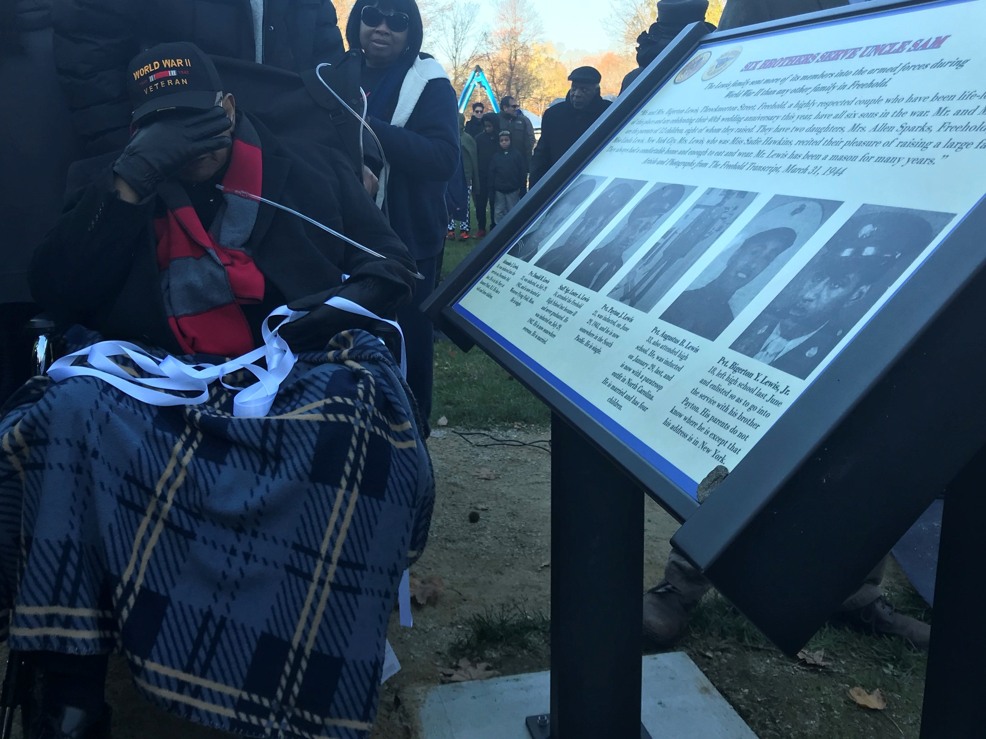 """Bigerton """"Buddy"""" Lewis Jr., covers his face as he sheds tears after the unveiling of the marker dedicated to him and his five late brothers, who all served in World War II."""