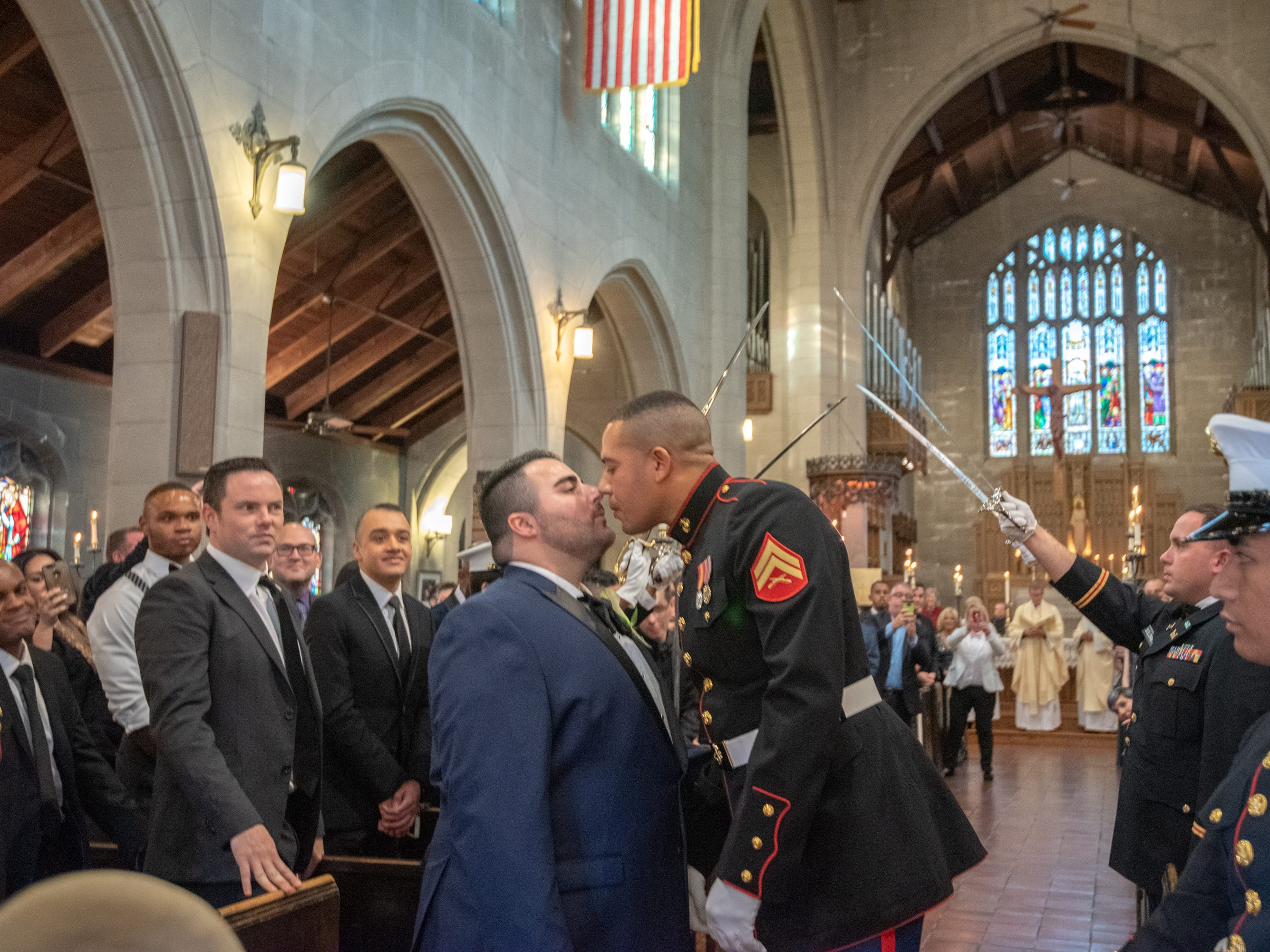 Christian Fuscarino, (left) Executive Director of Garden State Equality, and U.S. Marine Corporal Aaron Williams (in uniform) kiss as required during the raised sword ceremony. They were married at Trinity Church in Asbury Park on Sunday, November 11, 2018.