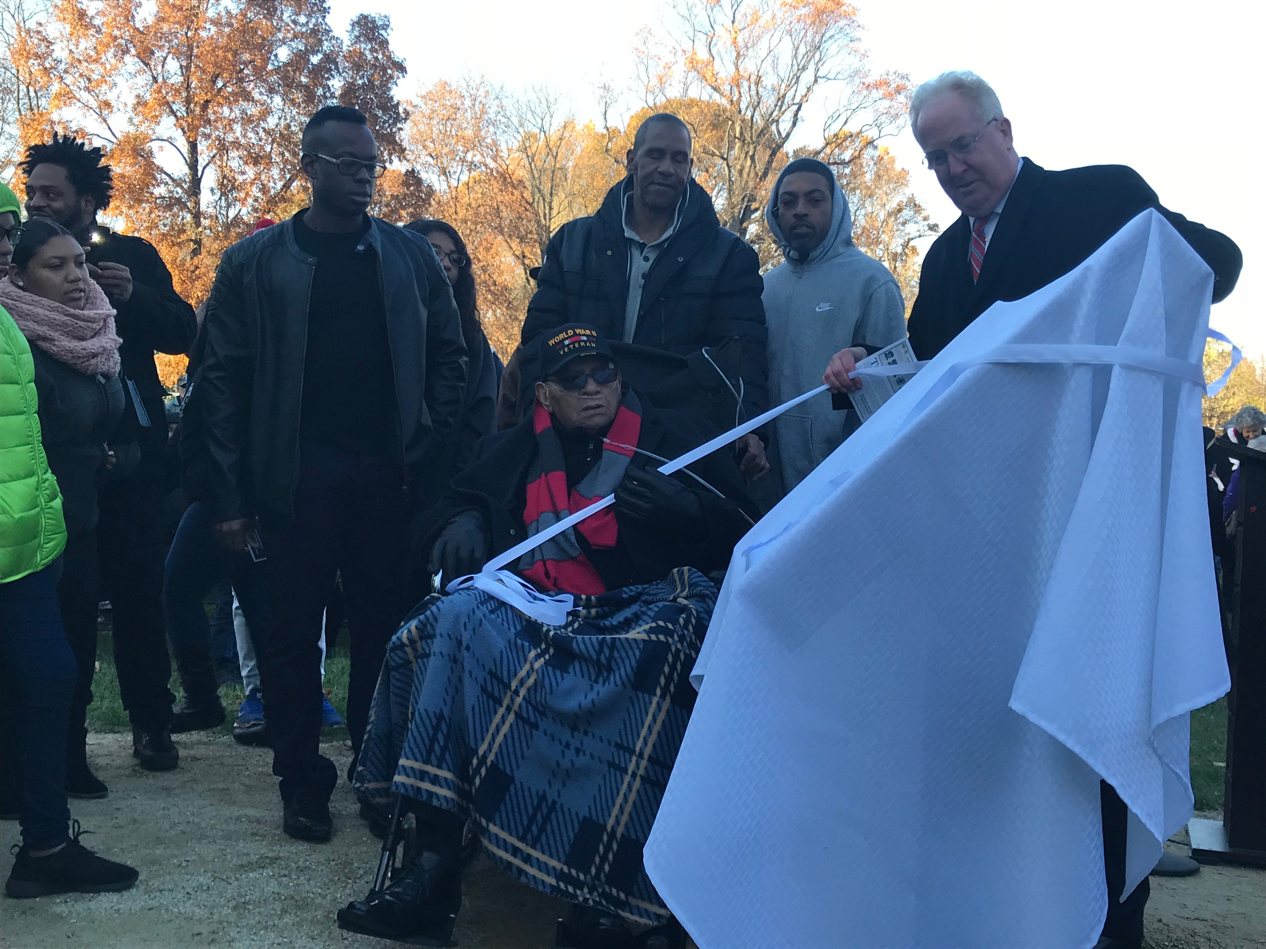 """Freehold Borough Mayor J. Nolan Higgins, right, and Bigerton """"Buddy"""" Lewis Jr., center, slowly unveil the marker dedicated to Lewis and his five brothers, who all served in World War II. The ceremony was held Sunday, Nov. 11, 2018, at Veterans Park."""