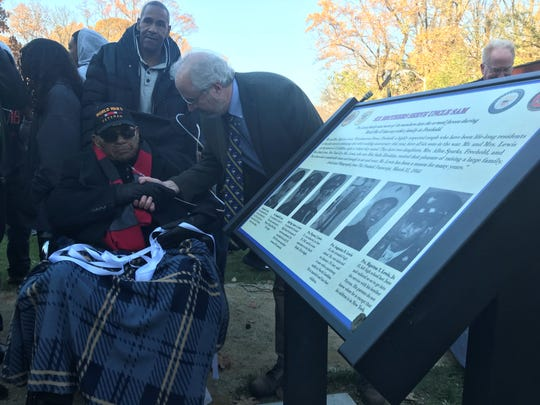 """Freehold Borough historian Kevin Coyne shakes hands with Bigerton """"Buddy"""" Lewis Jr. after the marker dedicating Lewis and his five brothers is unveiled at Veterans Park in Freehold Borough."""
