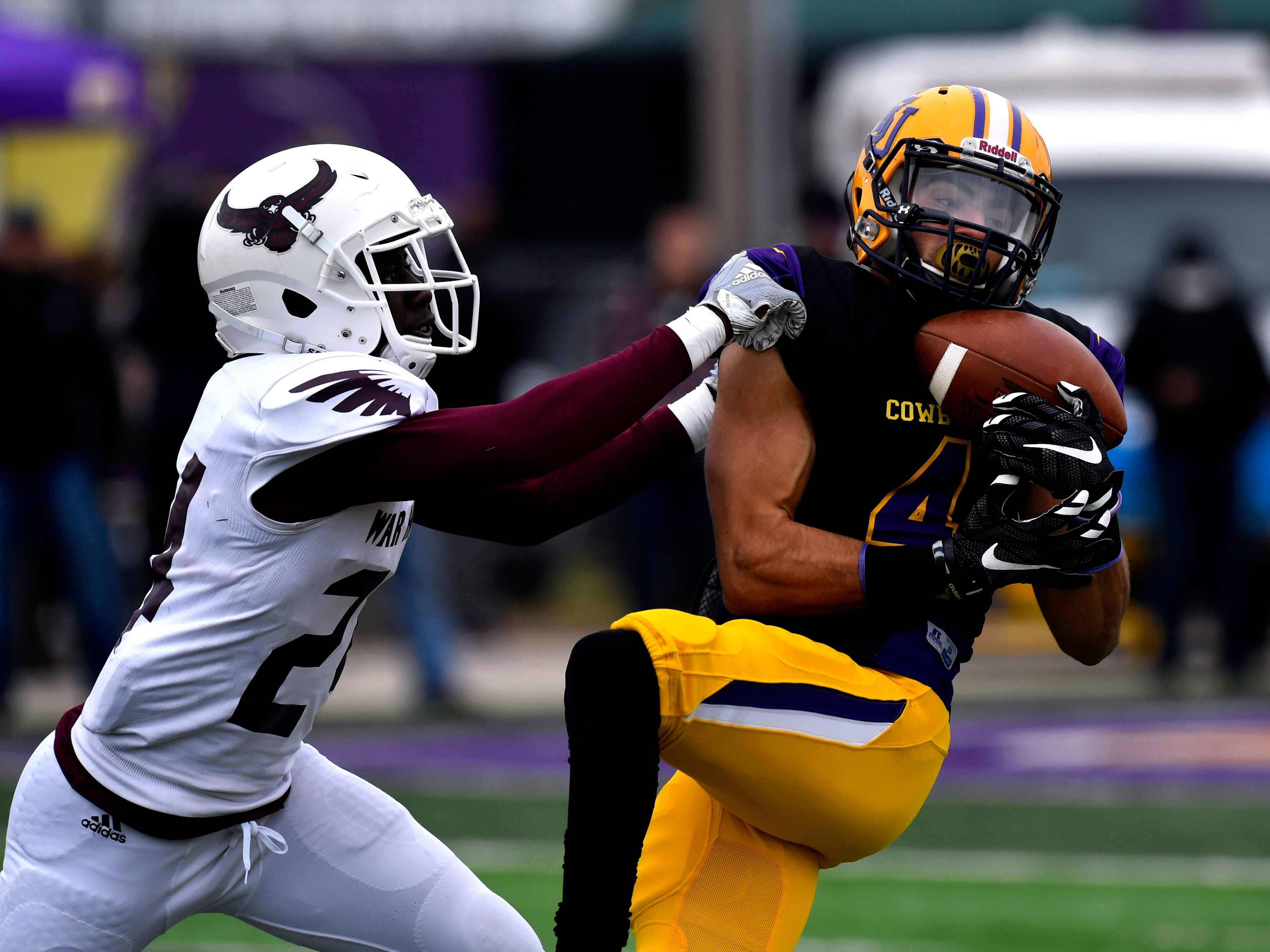Cowboys wide receiver Matthew Sandoval completes a pass as War Hawks defensive back Edward Coleman, jr. covers him for McMurry University Saturday Nov. 10, 2018. Final score was 83-6, Hardin-Simmons University.