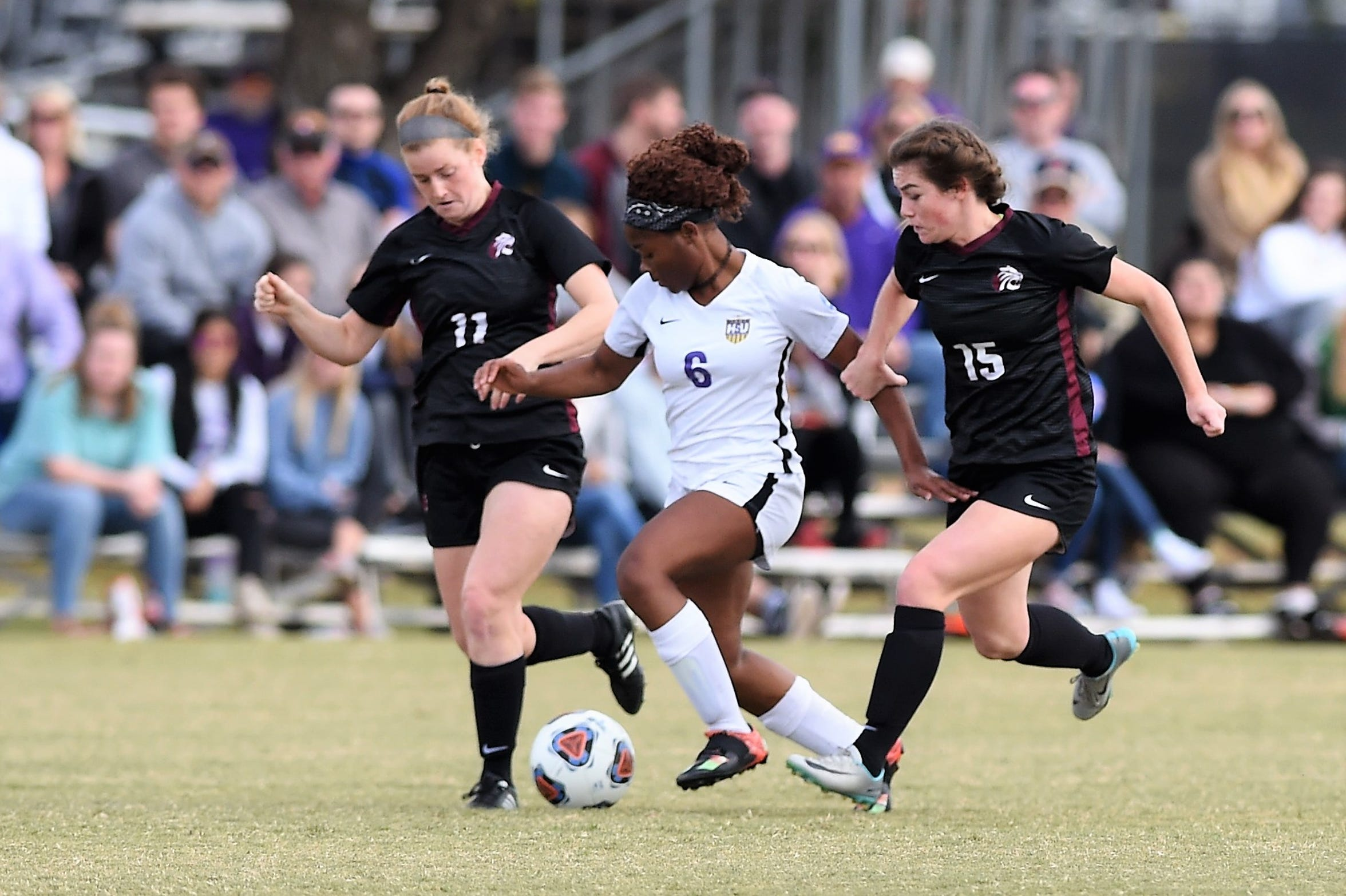 Hardin-Simmons forward Finda Kollie (6) attempts to split a pair of Trinity defenders in the second round of the 2018 NCAA Division III tournament. The Cowgirls reached the Sweet 16 for the 11th time in program history, all under head coach Marcus Wood.