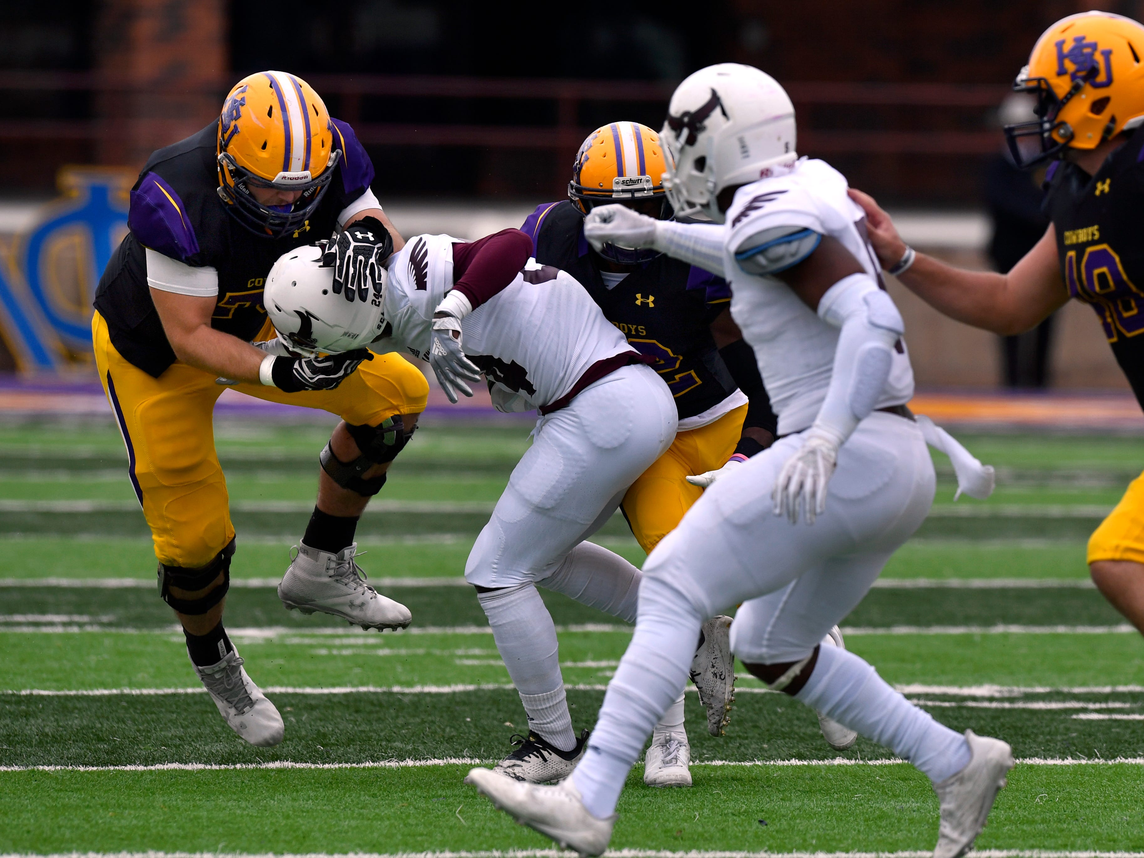 Cowboys offensive lineman Ty Crain wrenches the helmet of McMurry University defensive back Edward Coleman, jr., trying to clear the way for wide receiver Kevi Evans during Saturday's game Nov. 10, 2018. Final score was 83-6, Hardin-Simmons University.