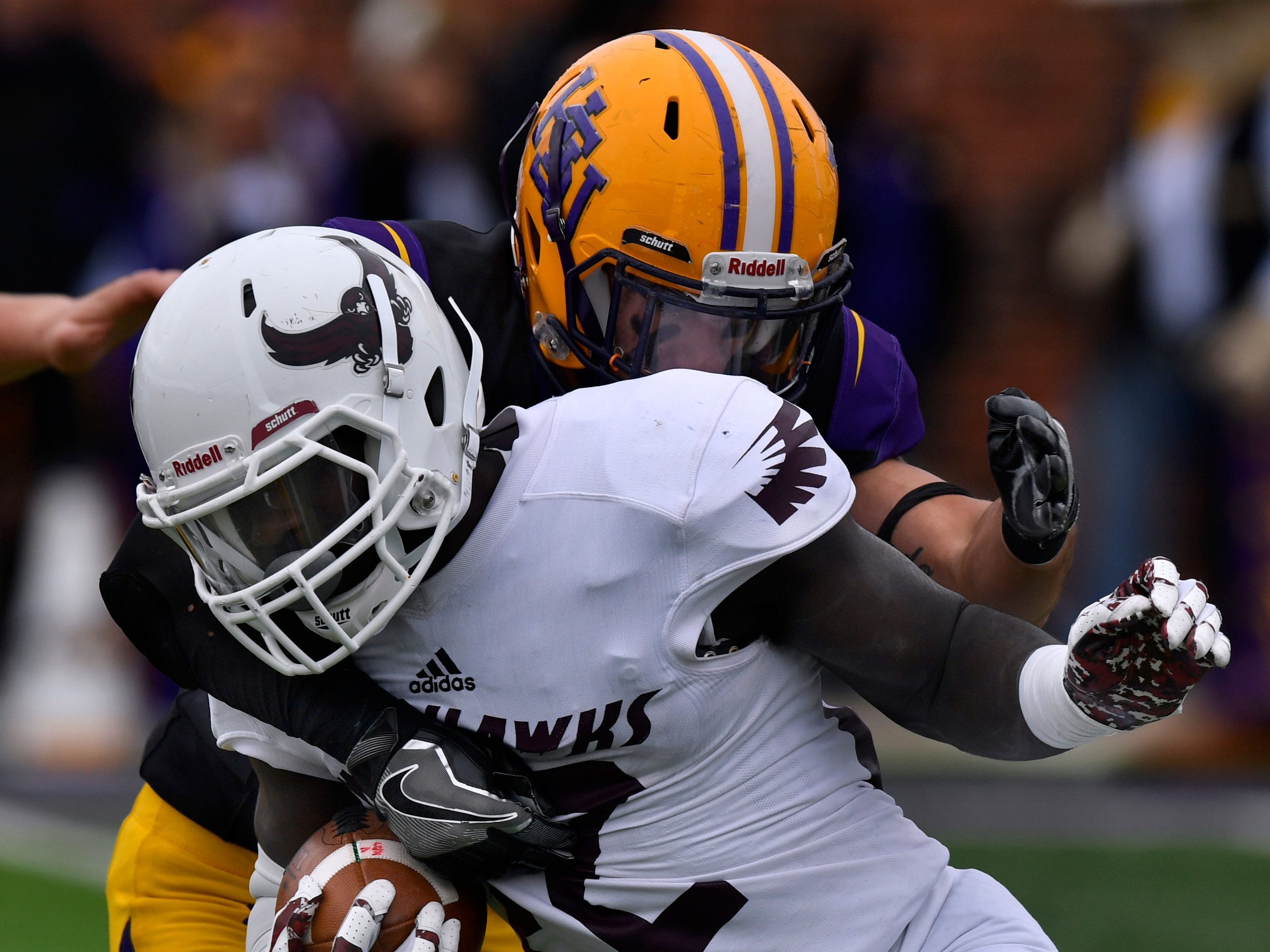 War Hawks running back Doyle Hughes is tackled by Cowboys safety Heriberto Elizondo during Saturday's game between Hardin-Simmons and McMurry universities. Final score was 83-6, HSU.