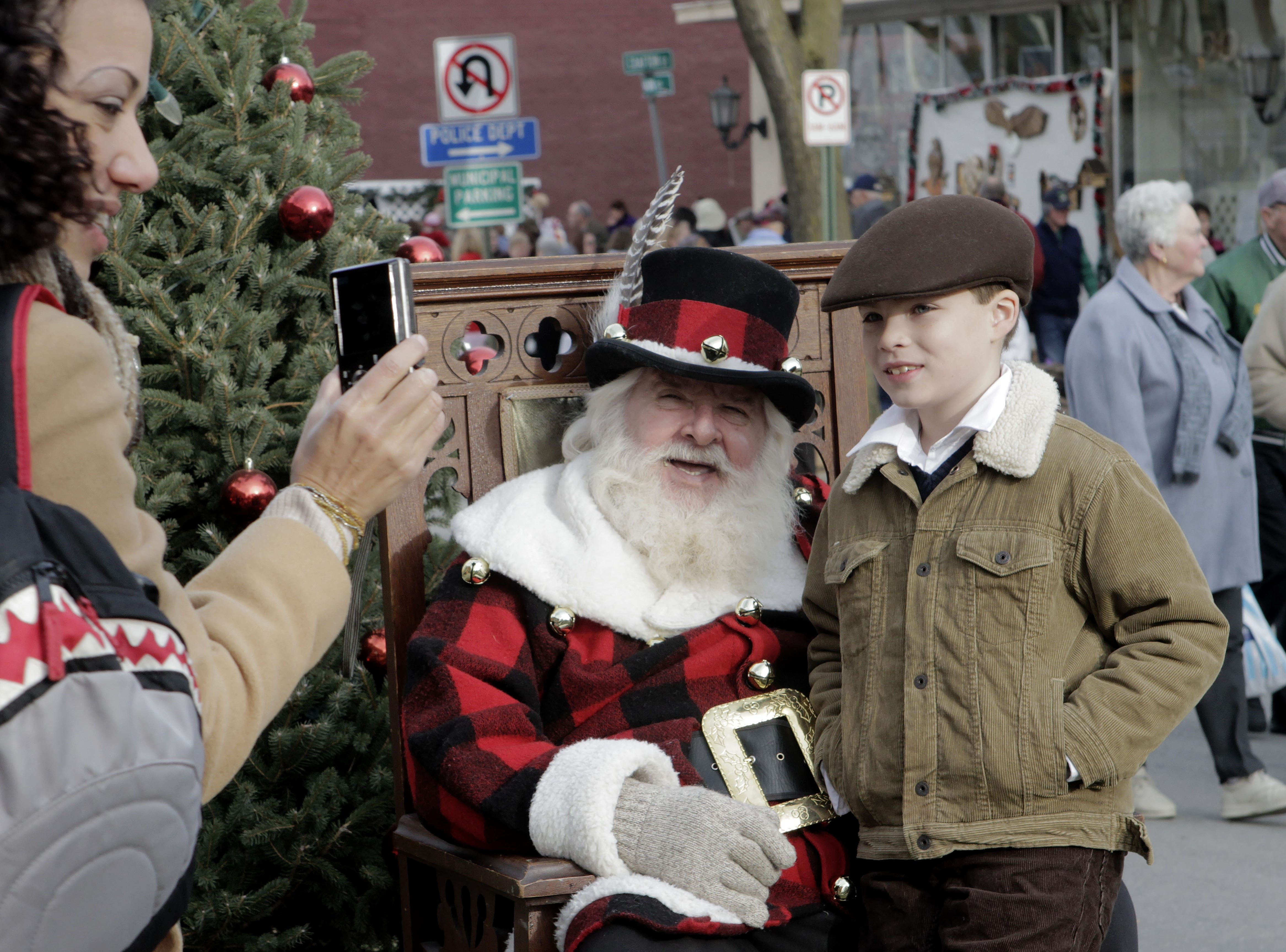 Visitors to the 2013 annual Dickens of a Christmas in Wellsboro snap photos with Santa Claus.