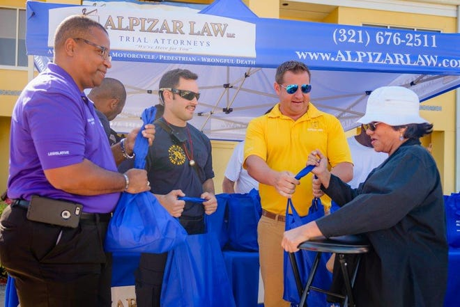 David Alpizar (yellow shirt) of Alpizar Law LLC and Palm Bay Mayor William Capote (far left) distribute free Thanksgiving turkeys at the law firm's free turkey giveaway last year.