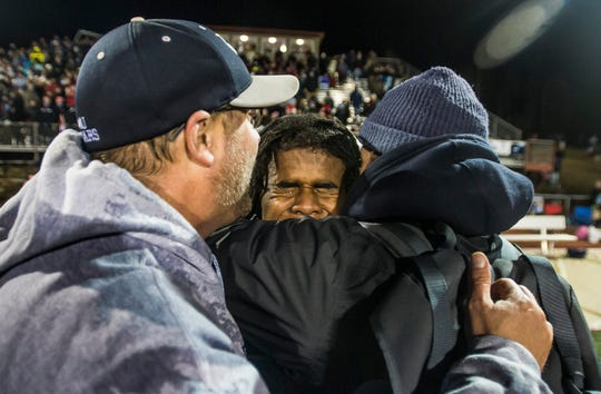 MMU's Jehric Hackney, center embraces his coaches after their Division I football championship against Rutland on Saturday, Nov. 11, 2018. Mount Mansfield won, 38-27.