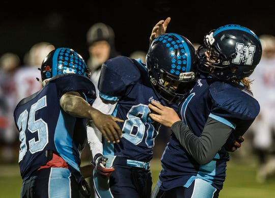 MMU's Mason Combs, center is congratulated after picking up the Rutland fumble for the possession during their Division I state football championship game in Rutland on Saturday, Nov. 10, 2018. Mount Mansfield won, 38-27.