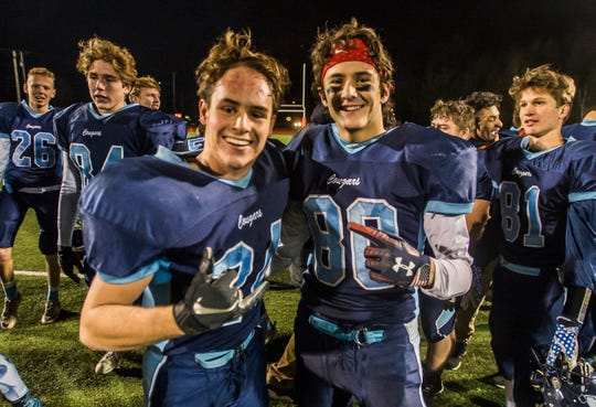 MMU's Bryce DiNardo (24) and Mason Combs (80) celebrate after their Division I football championship victory against Rutland on Saturday, Nov. 11, 2018. Mount Mansfield won over Rutland, 38-27.
