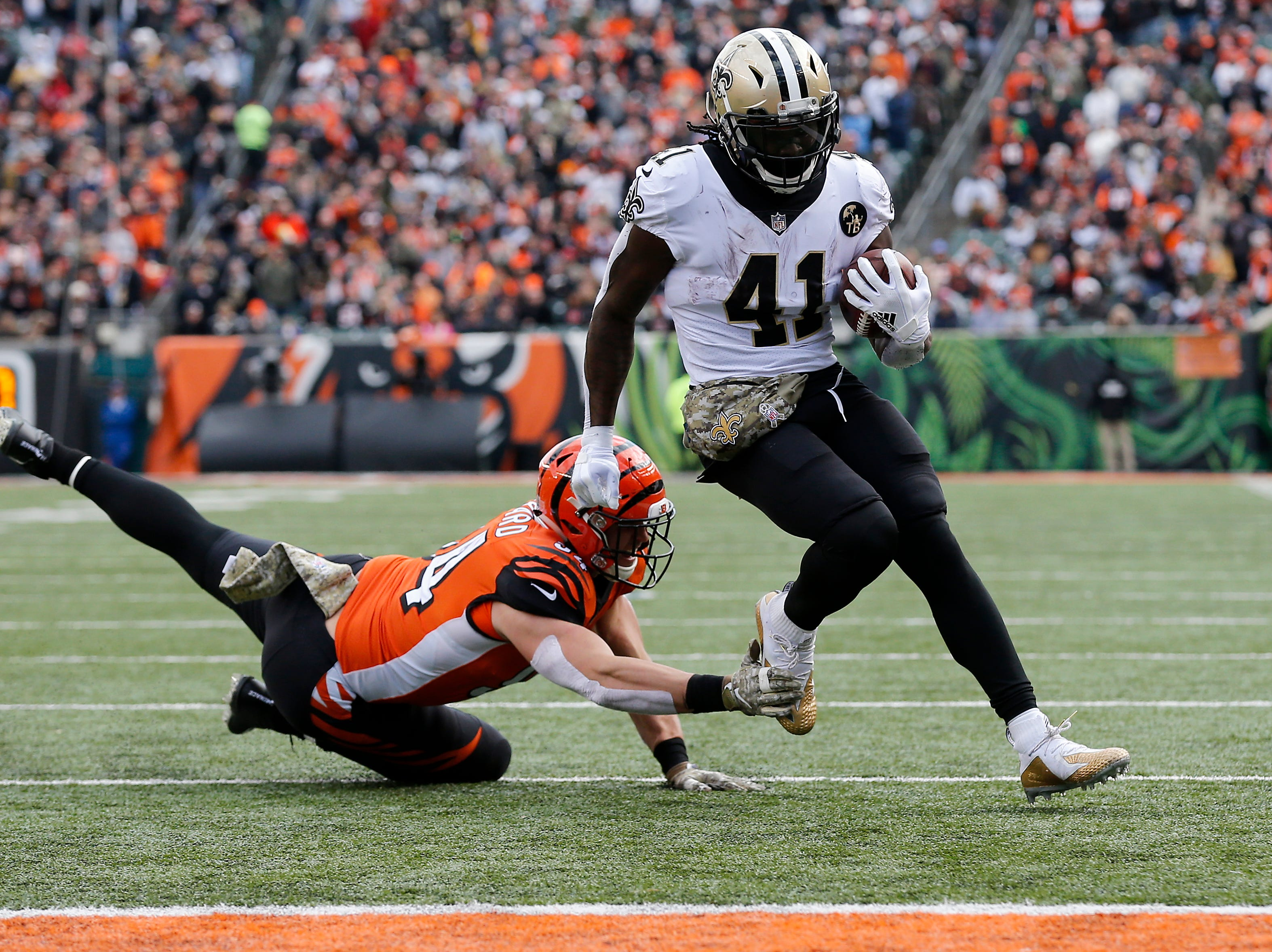 New Orleans Saints running back Alvin Kamara (41) high steps away from Cincinnati Bengals defensive end Sam Hubbard (94) for a touchdown in the second quarter of the NFL Week 10 game between the Cincinnati Bengals and the New Orleans Saints at Paul Brown Stadium in downtown Cincinnati on Sunday, Nov. 11, 2018. The Saints led 35-7 at halftime.
