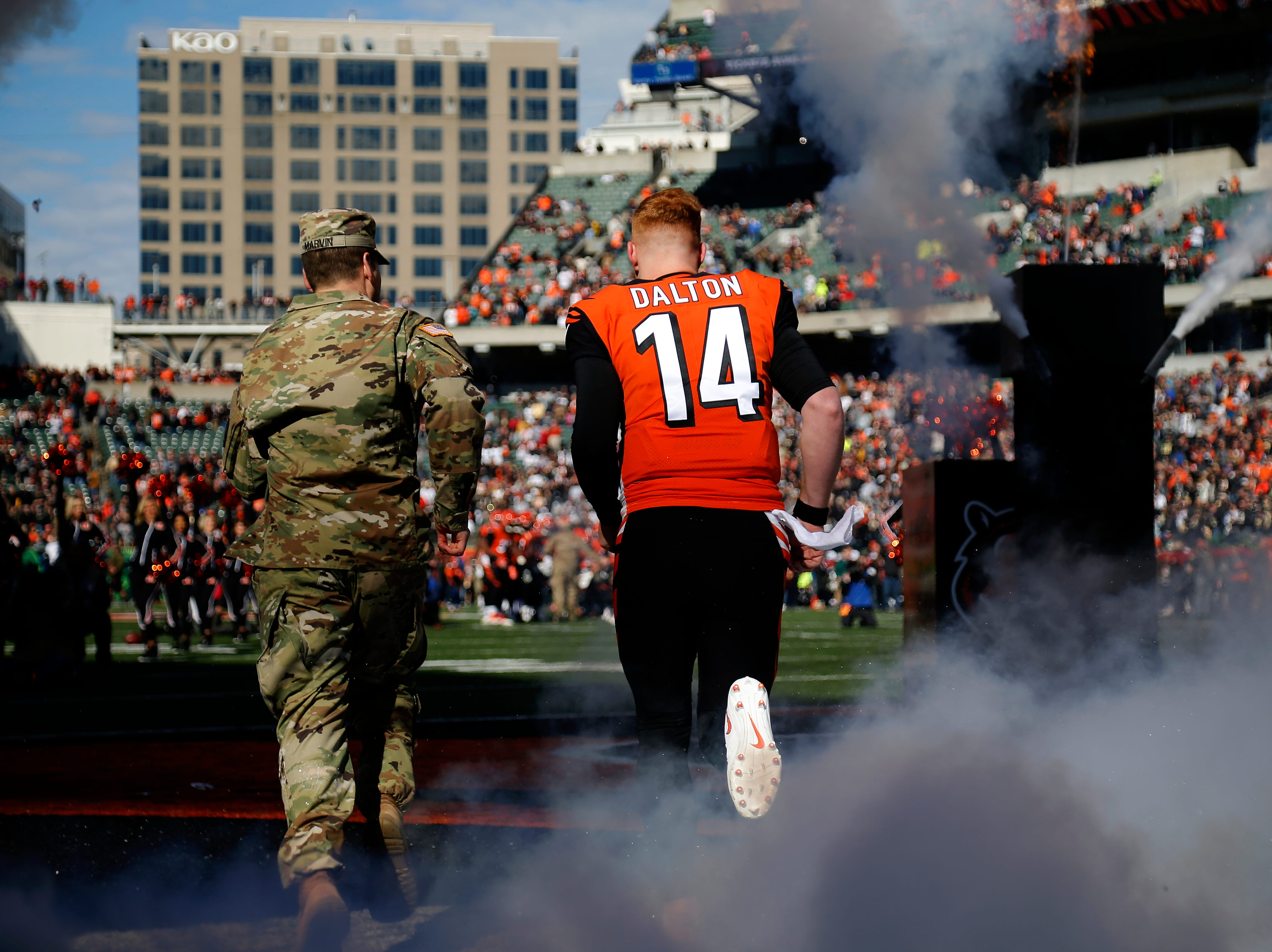 Cincinnati Bengals quarterback Andy Dalton (14) and his military escort take the field for the Salute to Service game before the first quarter of the NFL Week 10 game between the Cincinnati Bengals and the New Orleans Saints at Paul Brown Stadium in downtown Cincinnati on Sunday, Nov. 11, 2018. The Saints led 35-7 at halftime.