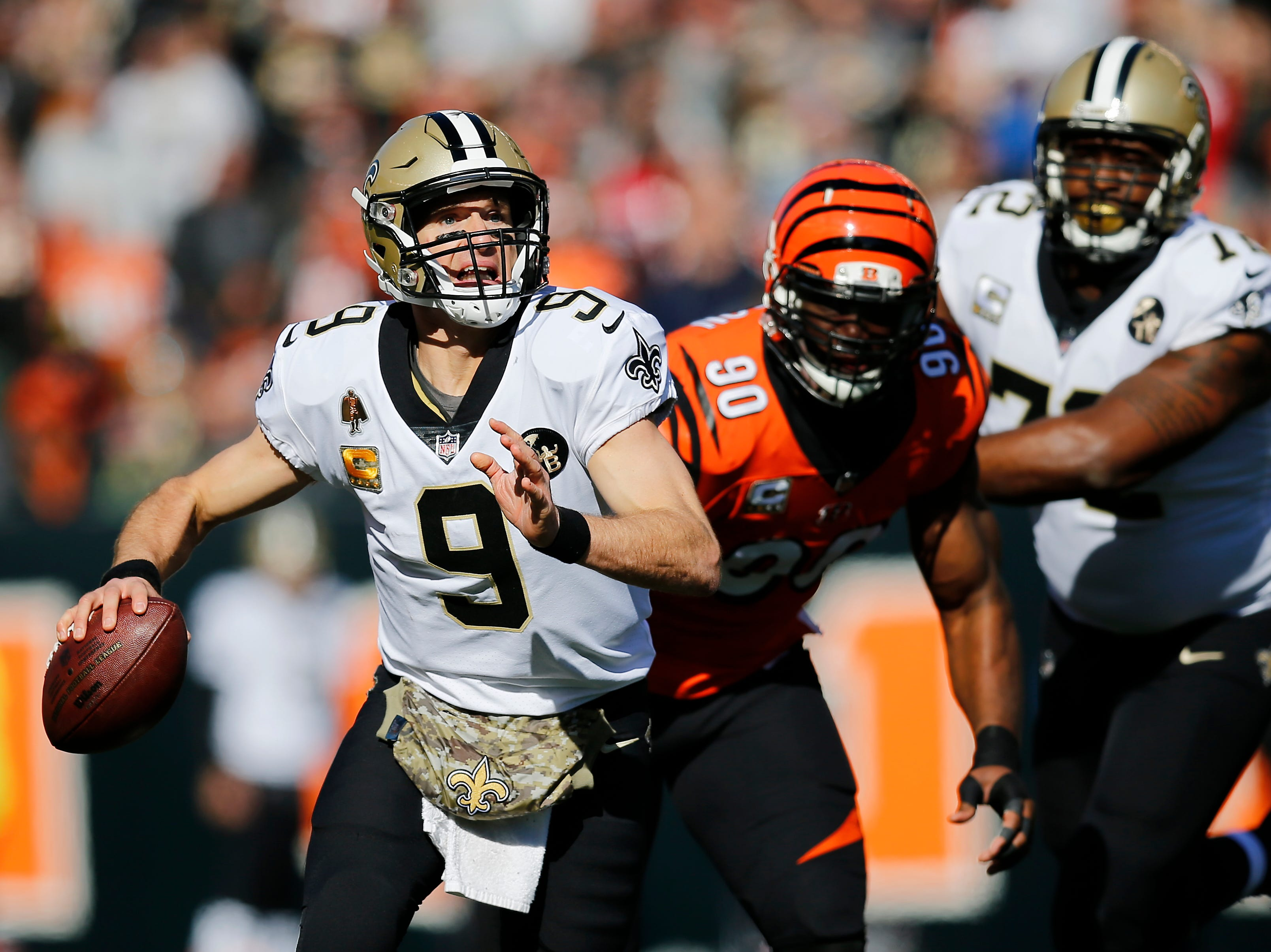 New Orleans Saints quarterback Drew Brees (9) scrambles as he's pursued by Cincinnati Bengals defensive end Michael Johnson (90) in the first quarter of the NFL Week 10 game between the Cincinnati Bengals and the New Orleans Saints at Paul Brown Stadium in downtown Cincinnati on Sunday, Nov. 11, 2018. The Saints led 35-7 at halftime.