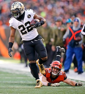 New Orleans Saints running back Mark Ingram (22) breaks a tackle from Cincinnati Bengals defensive end Sam Hubbard (94) on his way to a touchdown in the second quarter of the NFL Week 10 game between the Cincinnati Bengals and the New Orleans Saints at Paul Brown Stadium in downtown Cincinnati on Sunday, Nov. 11, 2018. The Saints led 35-7 at halftime.
