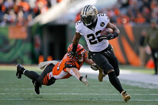 New Orleans Saints running back Mark Ingram (22) outruns a tackle attempt from Cincinnati Bengals defensive end Sam Hubbard (94) on his way to a touchdown in the second quarter of the NFL Week 10 game between the Cincinnati Bengals and the New Orleans Saints at Paul Brown Stadium in downtown Cincinnati on Sunday, Nov. 11, 2018. The Saints led 35-7 at halftime.