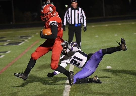 Madison's Gabe Higgs runs past CHCA's Alex Bernard (21) to bring the final score to 50-06 in favor of the Mohawks at the Division V region semifinal, November 10, 2018