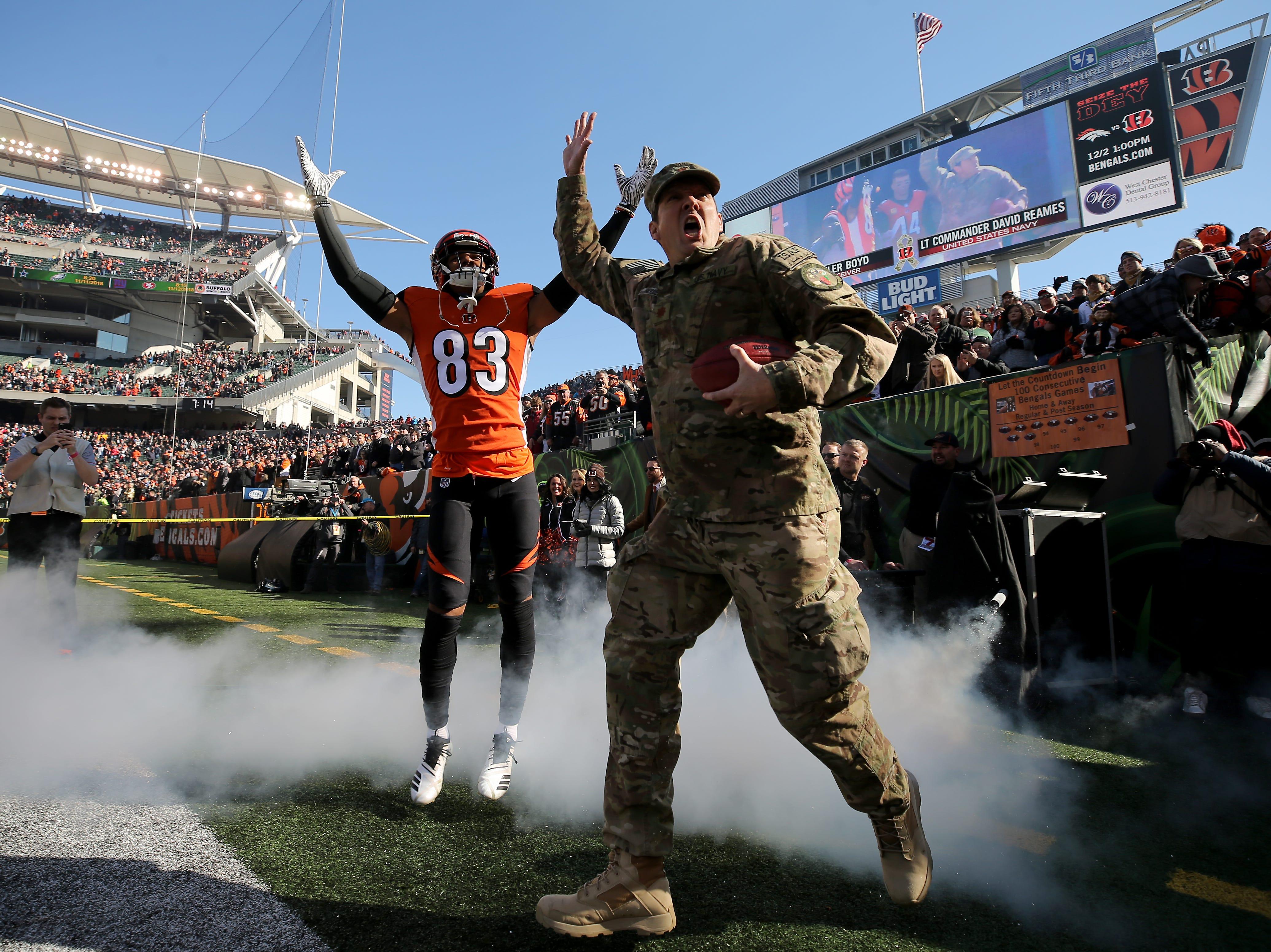 Navy Lt. Commander David Reames, right, is introduced with Cincinnati Bengals wide receiver Tyler Boyd (83) before the Week 10 NFL game between the New Orleans Saints and the Cincinnati Bengals, Sunday, Nov. 11, 2018, at Paul Brown Stadium in Cincinnati.