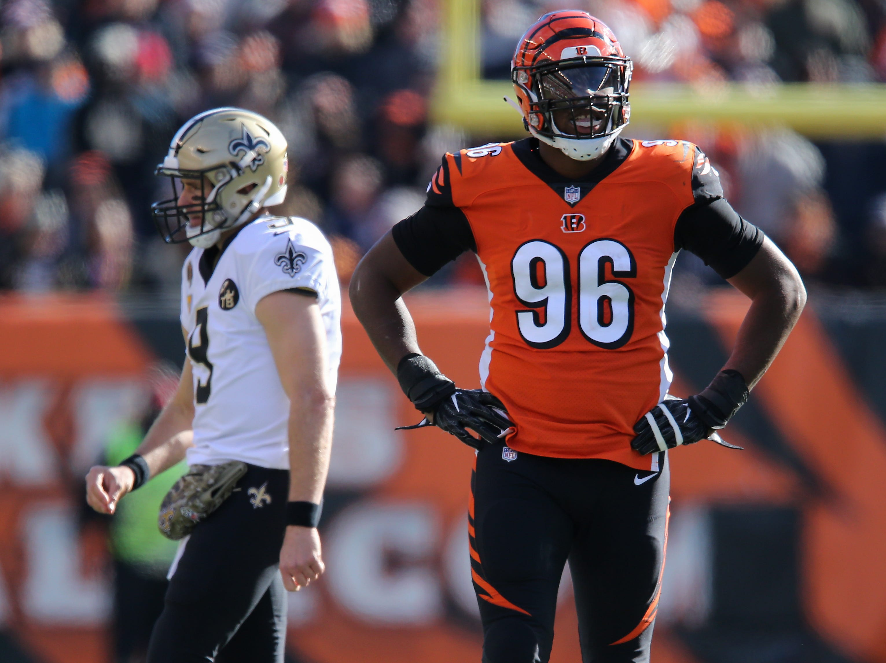 Cincinnati Bengals defensive end Carlos Dunlap (96) smiles and rests his hands on his hips as New Orleans Saints quarterback Drew Brees (9) walks in the background in the second quarter of a Week 10 NFL game between the New Orleans Saints and the Cincinnati Bengals, Sunday, Nov. 11, 2018, at Paul Brown Stadium in Cincinnati.