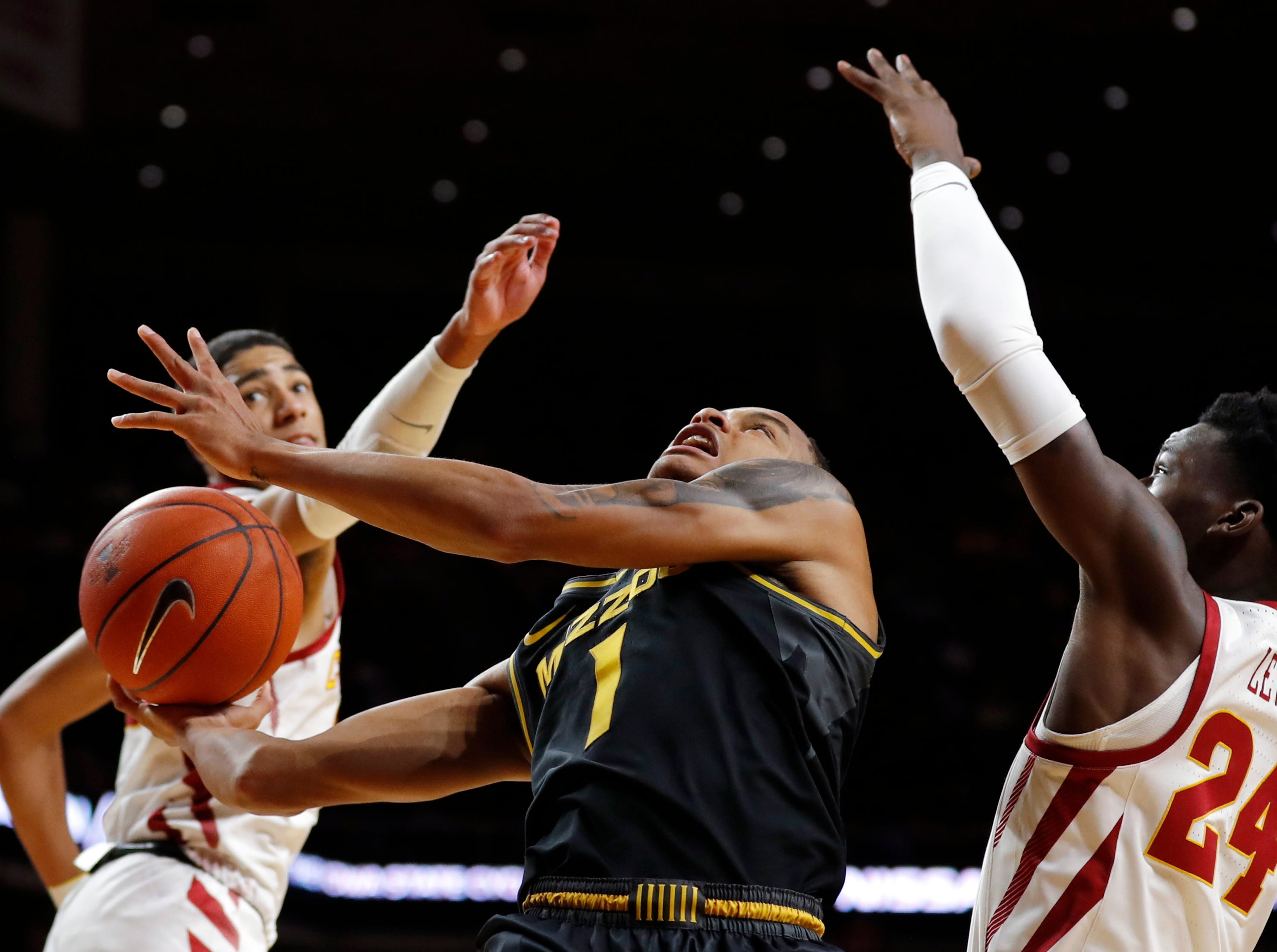 Missouri guard Xavier Pinson, center, drives to the basket between Iowa State's Tyrese Haliburton, left, and Terrence Lewis during the second half of an NCAA college basketball game, Friday, Nov. 9, 2018, in Ames, Iowa. Iowa State won 76-59.