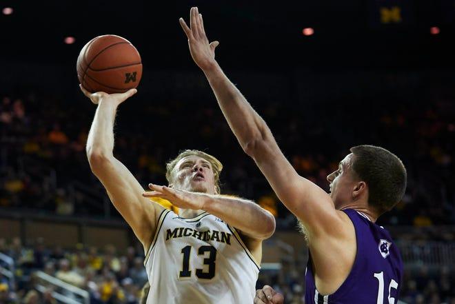 Michigan forward Ignas Brazdeikis shoots against Holy Cross forward Matt Faw in the first half at Crisler Center, Nov. 10, 2018 in Ann Arbor.