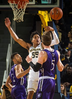 Michigan guard Eli Brooks tries to intercept a pass from Holy Cross forward Connor Niego (5) to guard Kyle Copeland during the first half in Ann Arbor, Saturday, Nov. 10, 2018.