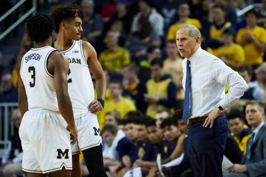 Michigan coach John Beilein talks to guards Zavier Simpson and Jordan Poole in the first half against Holy Cross at Crisler Center, Nov. 10, 2018 in Ann Arbor.