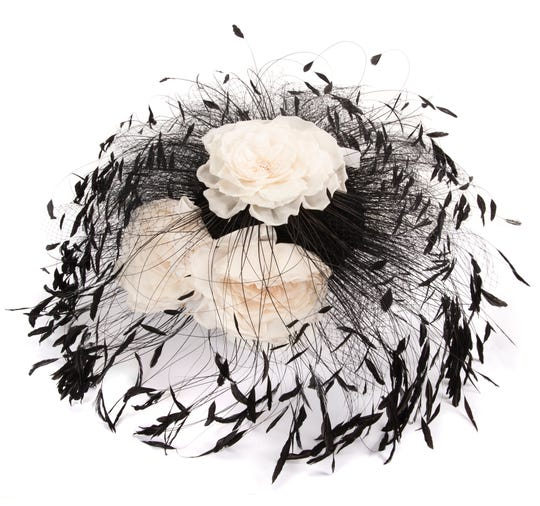 "A small black silk hat adorned with elaborate black feathers, black fishnet, and three large white silk flowers, labels  reads ""Philip Treacy / London"" and ""Made in England / for Bergdorf  / Goodman;"" worn by the singer during  the grand opening ceremony at the Rock & Roll Hall of Fame on Sept. 7,  1995. It sold for $3,125 from Julien's Auctions."