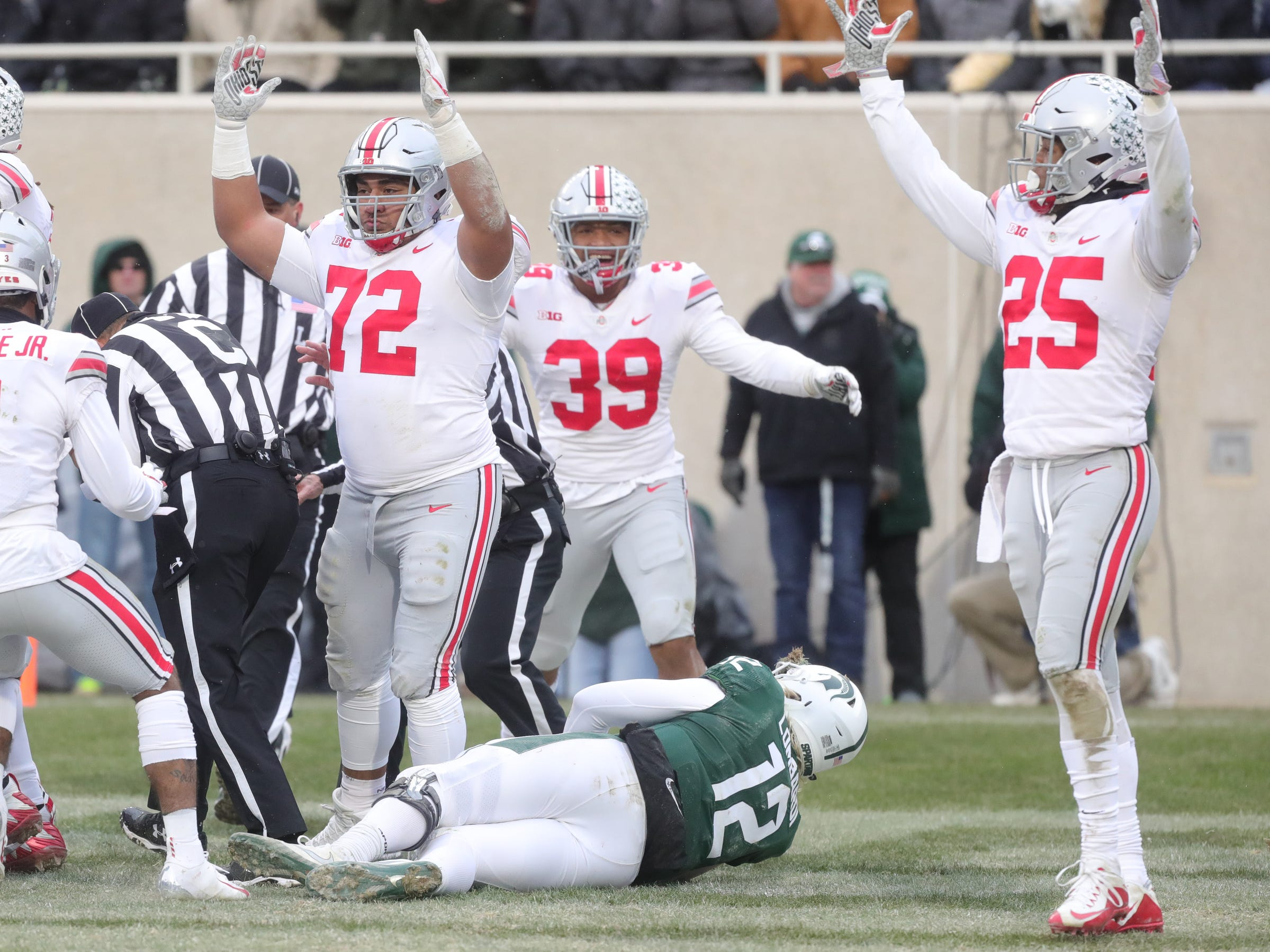 Michigan State's Rocky Lombardi fumbles Ohio State's Jonathon Cooper, who would recover the ball for a touchdown during the second half of the 26-6 loss to Ohio State on Saturday, Nov. 10, 2018, in East Lansing.