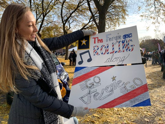 Samantha Winnie, of Taylor, shows off the patriotic posters she made to honor her grandfather, Korean War army veteran Jimmy 'Fergie' Ferguson at the Detroit Veterans Day Parade on Sunday, Nov. 11, 2018.