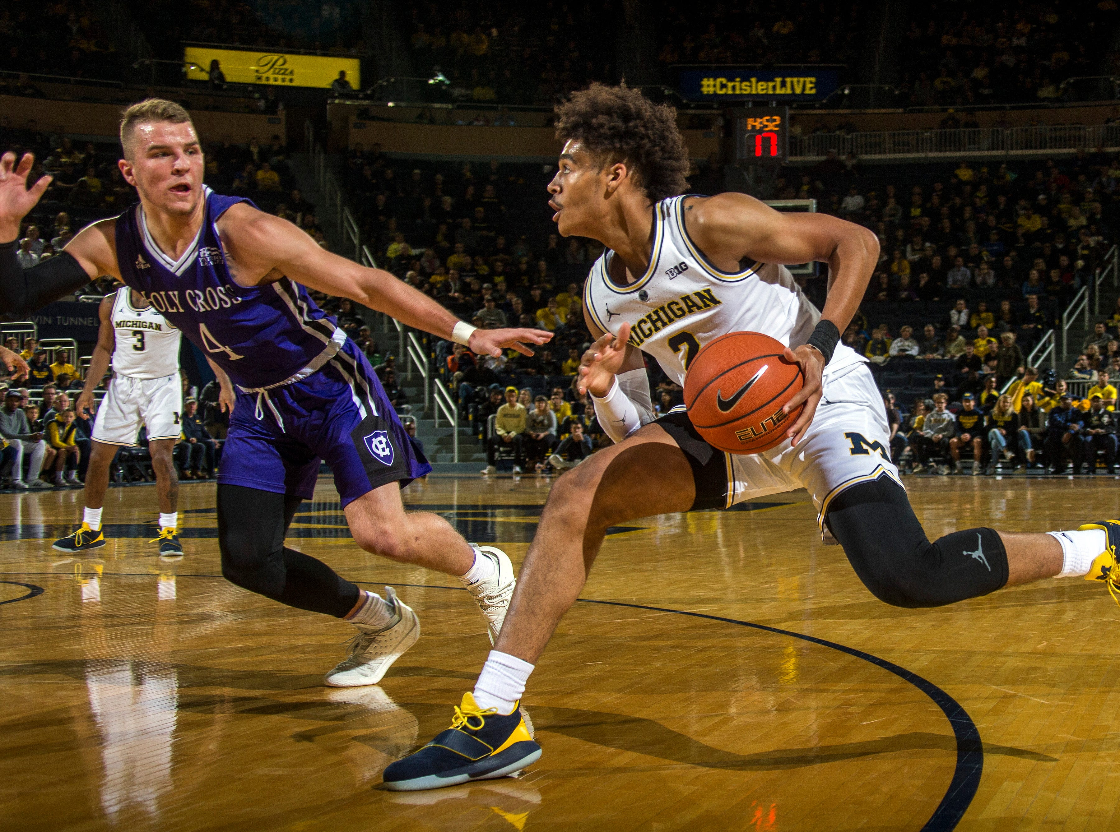 Holy Cross guard Austin Butler (4) defends Michigan guard Jordan Poole (2) in the first half of an NCAA college basketball game at Crisler Center in Ann Arbor, Mich., Saturday, Nov. 10, 2018. Michigan won 56-37. (AP Photo/Tony Ding)
