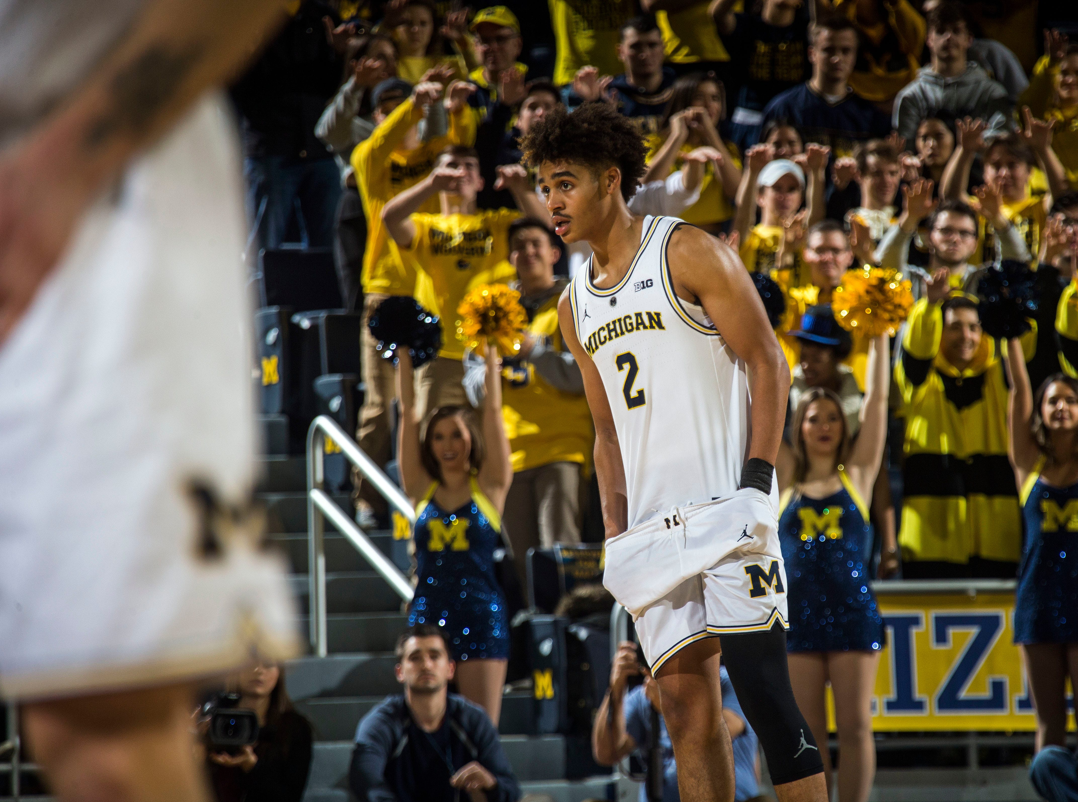 Michigan guard Jordan Poole (2) adjusts his shorts on court during a free throw in the second half of an NCAA college basketball game against Holy Cross at Crisler Center in Ann Arbor, Mich., Saturday, Nov. 10, 2018. Michigan won 56-37. (AP Photo/Tony Ding)
