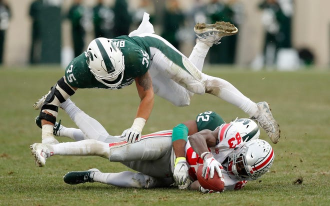 Michigan State linebacker Joe Bachie flips over Michigan State cornerback Josiah Scott as Scott tackles Ohio State wide receiver Terry McLaurin.