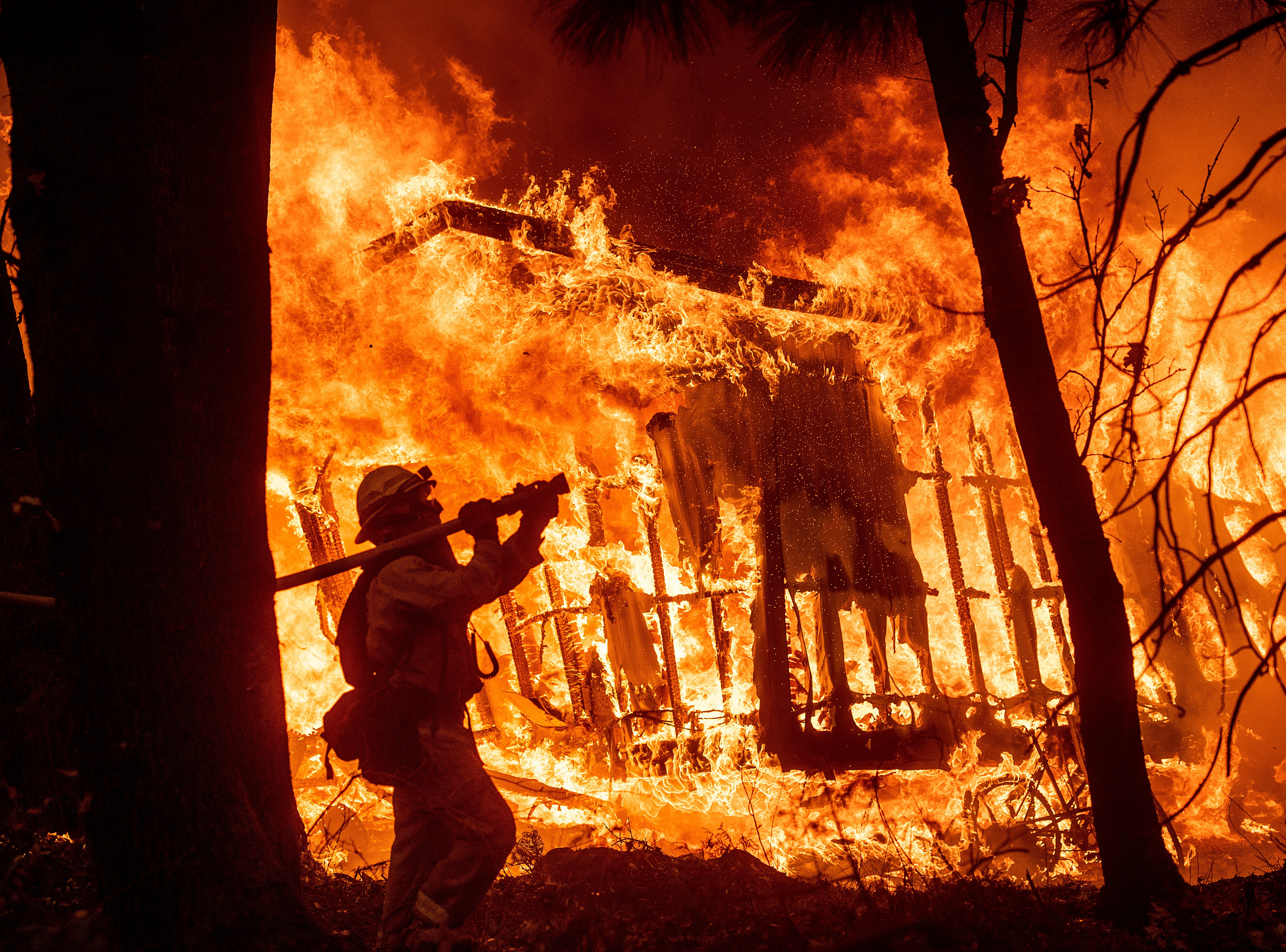 Firefighter Jose Corona sprays water as flames from the Camp Fire consume a home in Magalia, Calif., on Friday, Nov. 9, 2018.