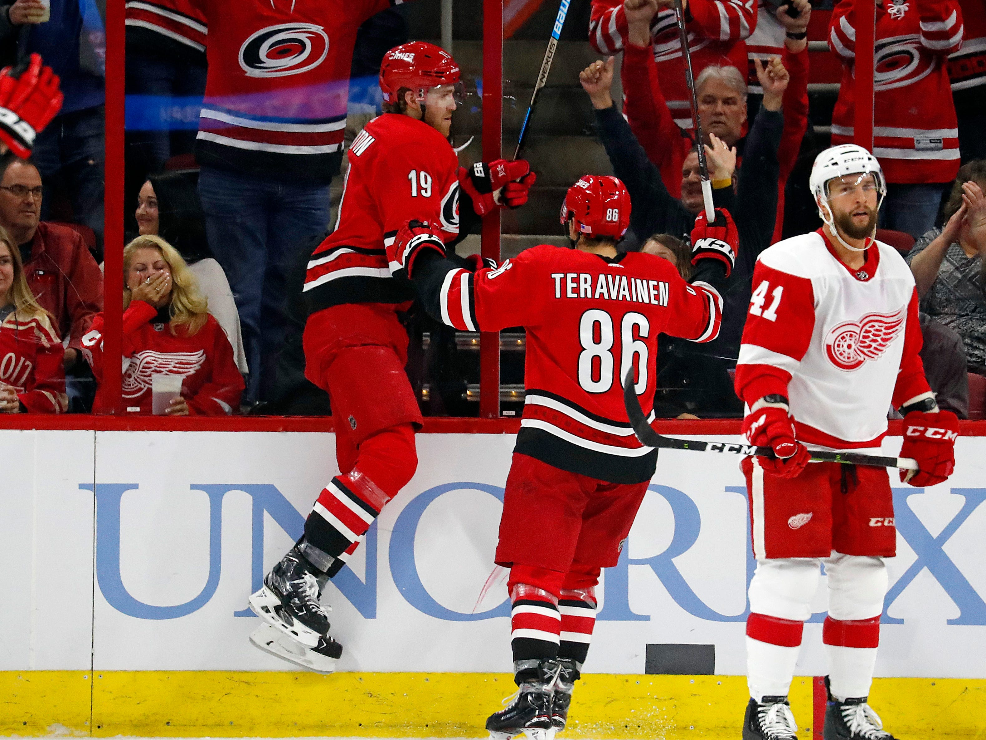 Carolina Hurricanes' Dougie Hamilton (19) and Teuvo Teravainen celebrate Hamilton's goal as Detroit Red Wings' Luke Glendening (41) skates away during the second period.